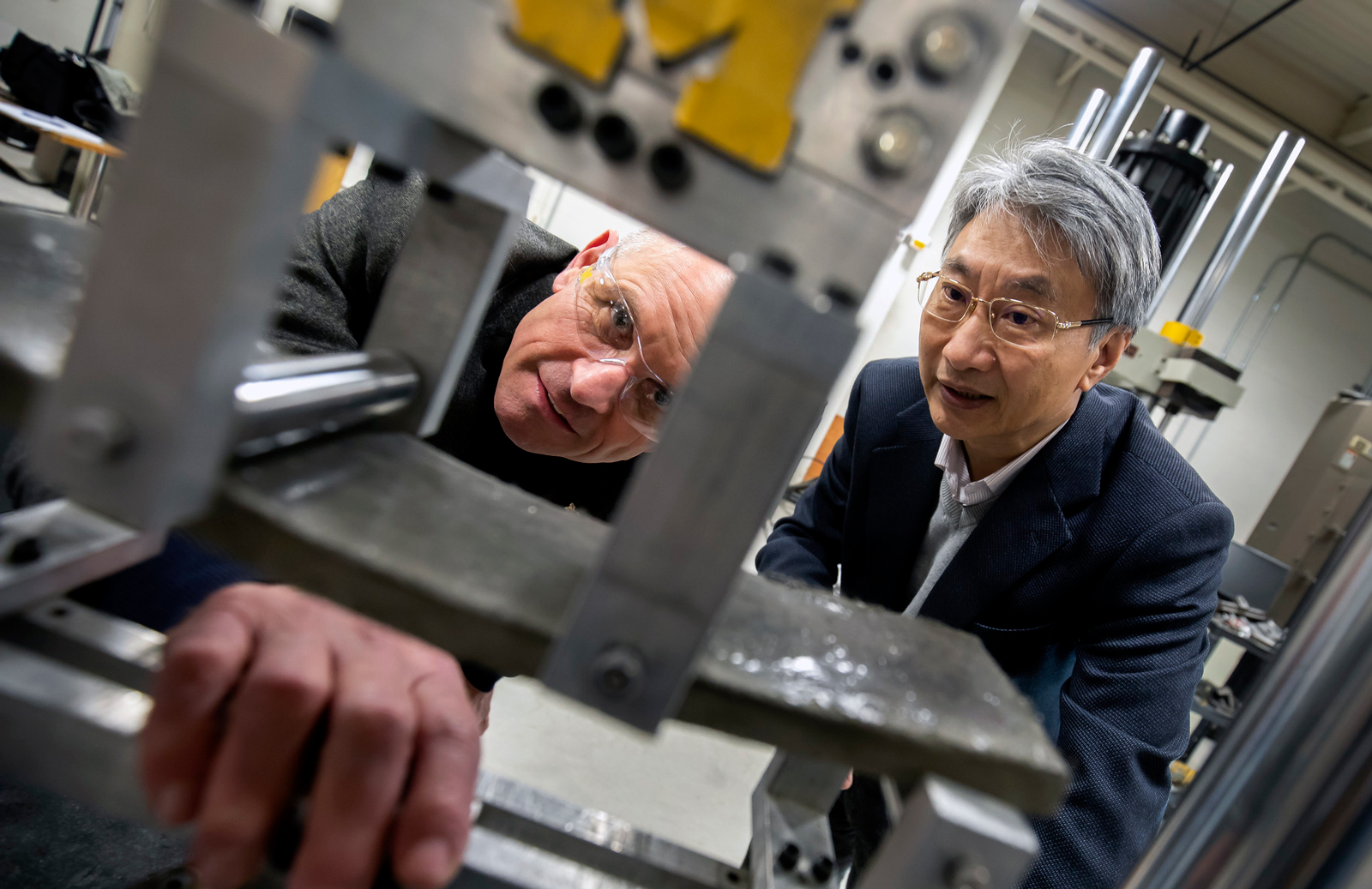 Volker Sick, director of the Global CO2 Initiative, and Victor Li, the James R. Rice Distinguished University Professor of Engineering and E. Benjamin Wylie Collegiate Professor of Civil Engineering, watch as a piece of bendable concrete infused with CO2 undergoes a tensile test. Li's technology would sequester atmospheric CO2 in concrete. Photo: Joseph Xu/Michigan Engineering
