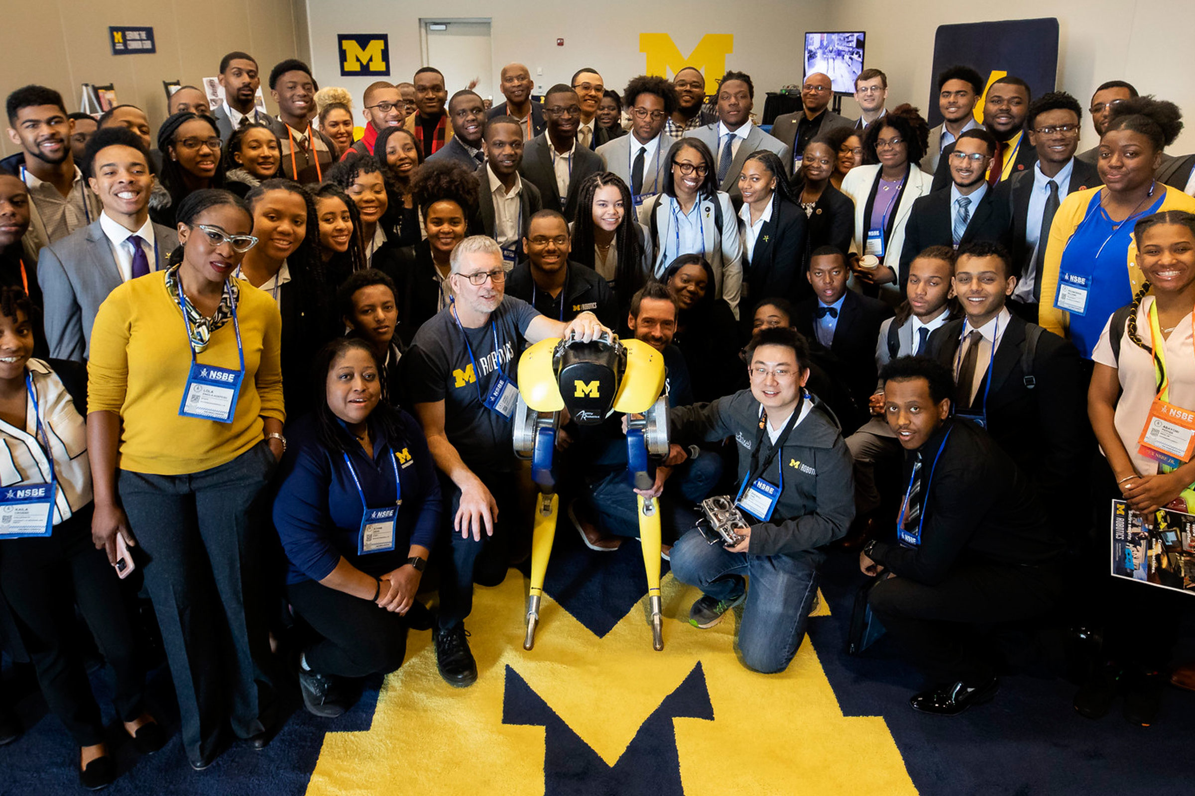 Group of NSBE members pose together with the bipedal robot, Cassie