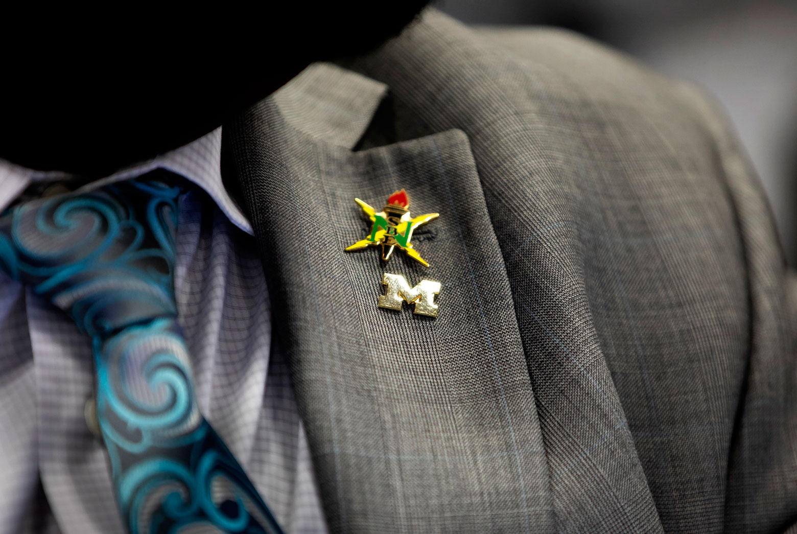 Close-up of the NSBE pin on a man's suit jacket