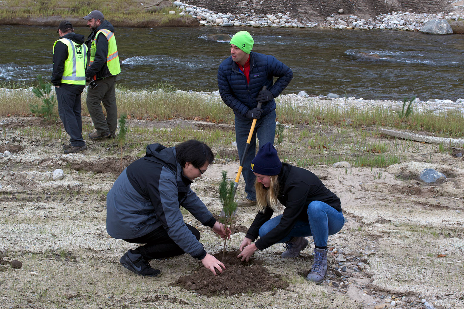 Three people plant small tree by river