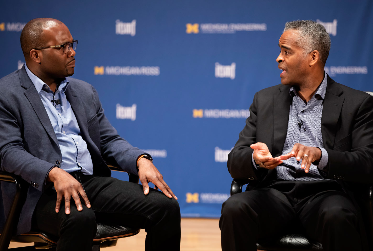 Ibrahim Jackson and Michael Jones talk while seated on a stage