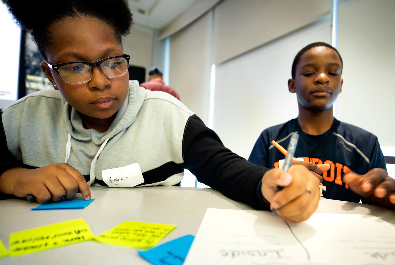 Two middle school students work on a design challenge
