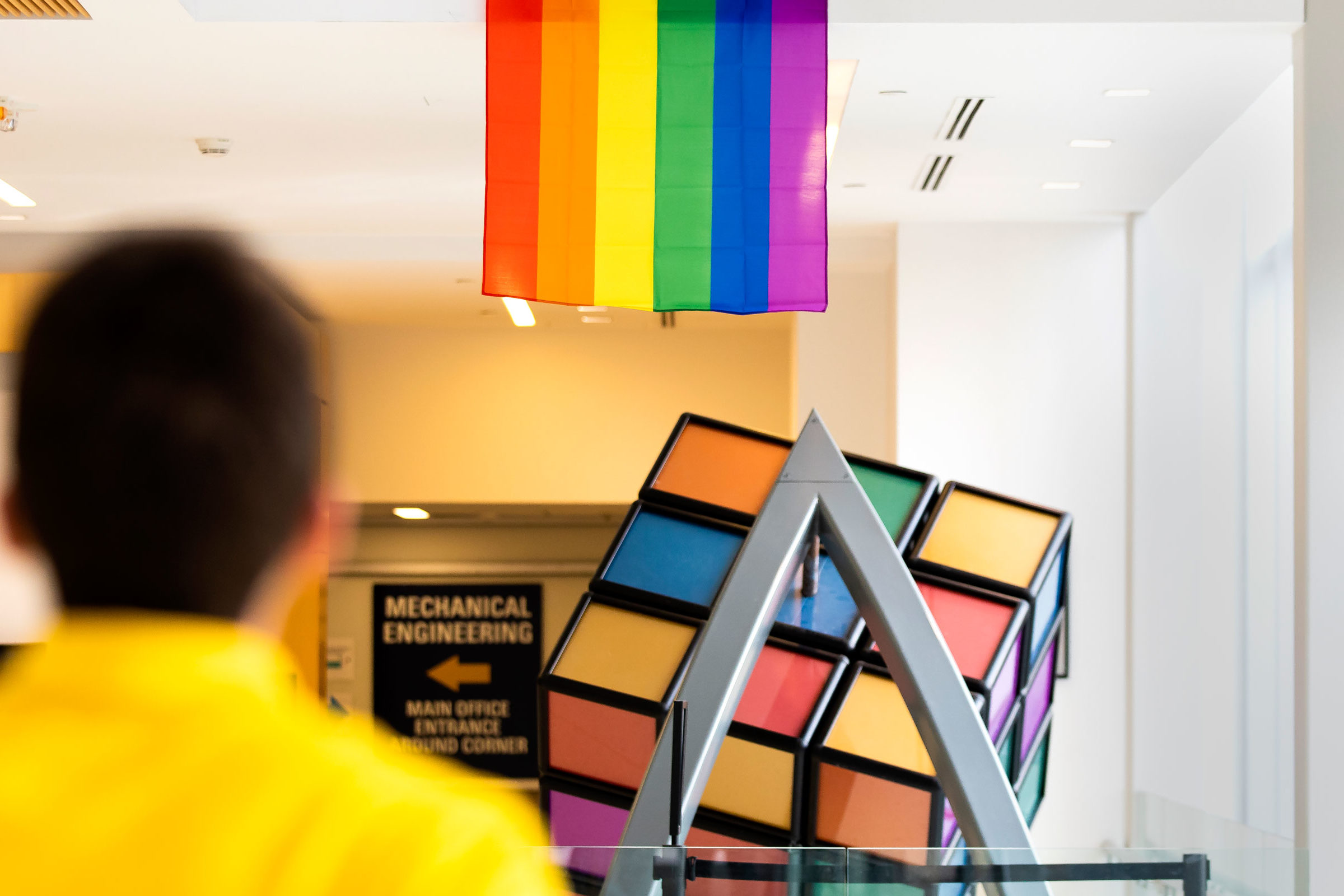 Back to the camera, student walks down the hall towards a giant Rubik's cube display and a rainbow flag