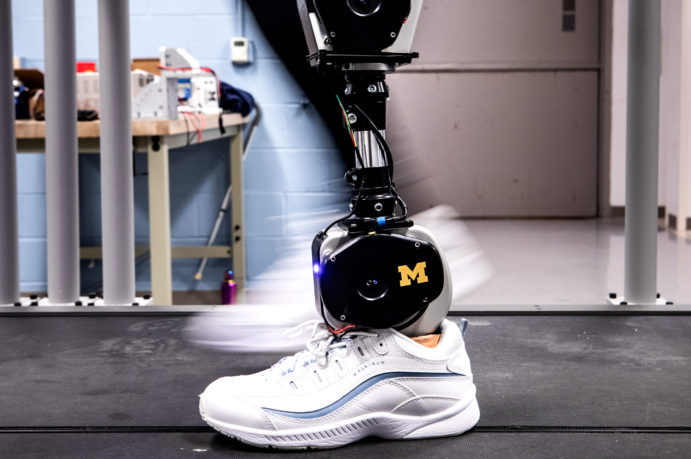 A robot leg practices walking on a treadmill