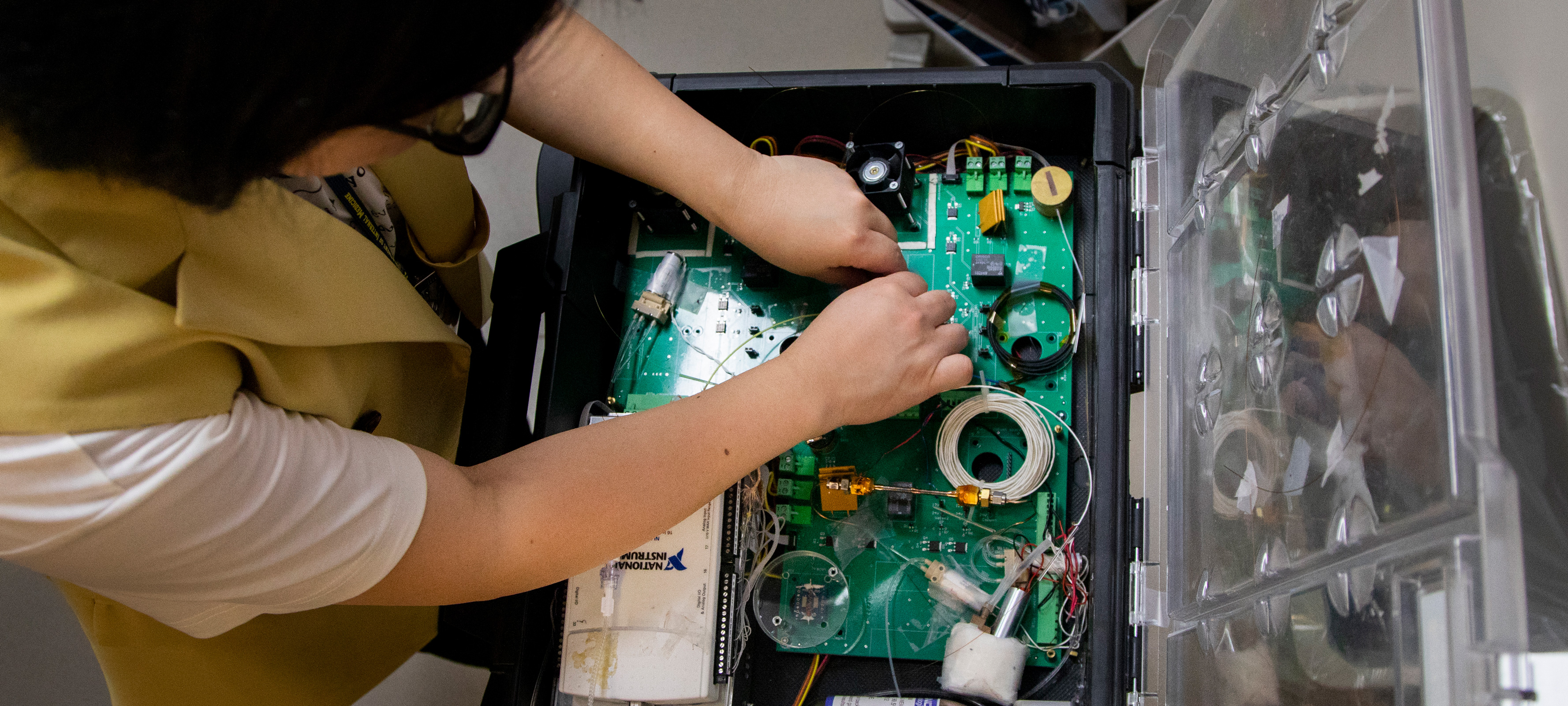 Biomedical Engineering graduate student research assistant Menglian Zhou, adjusts the lung monitoring device.