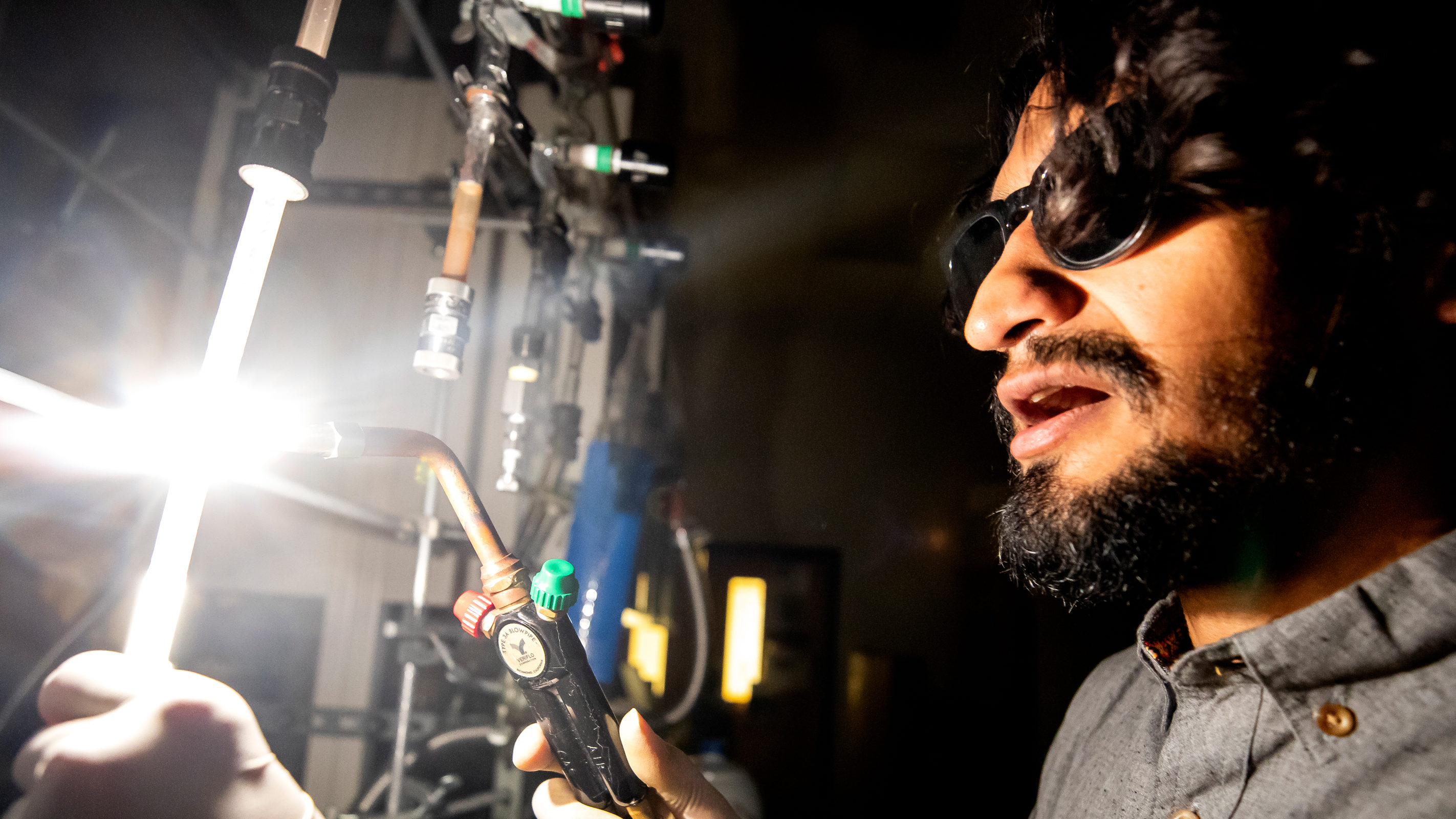 Juan Lopez wears sunglasses to protect his eyes in the lab