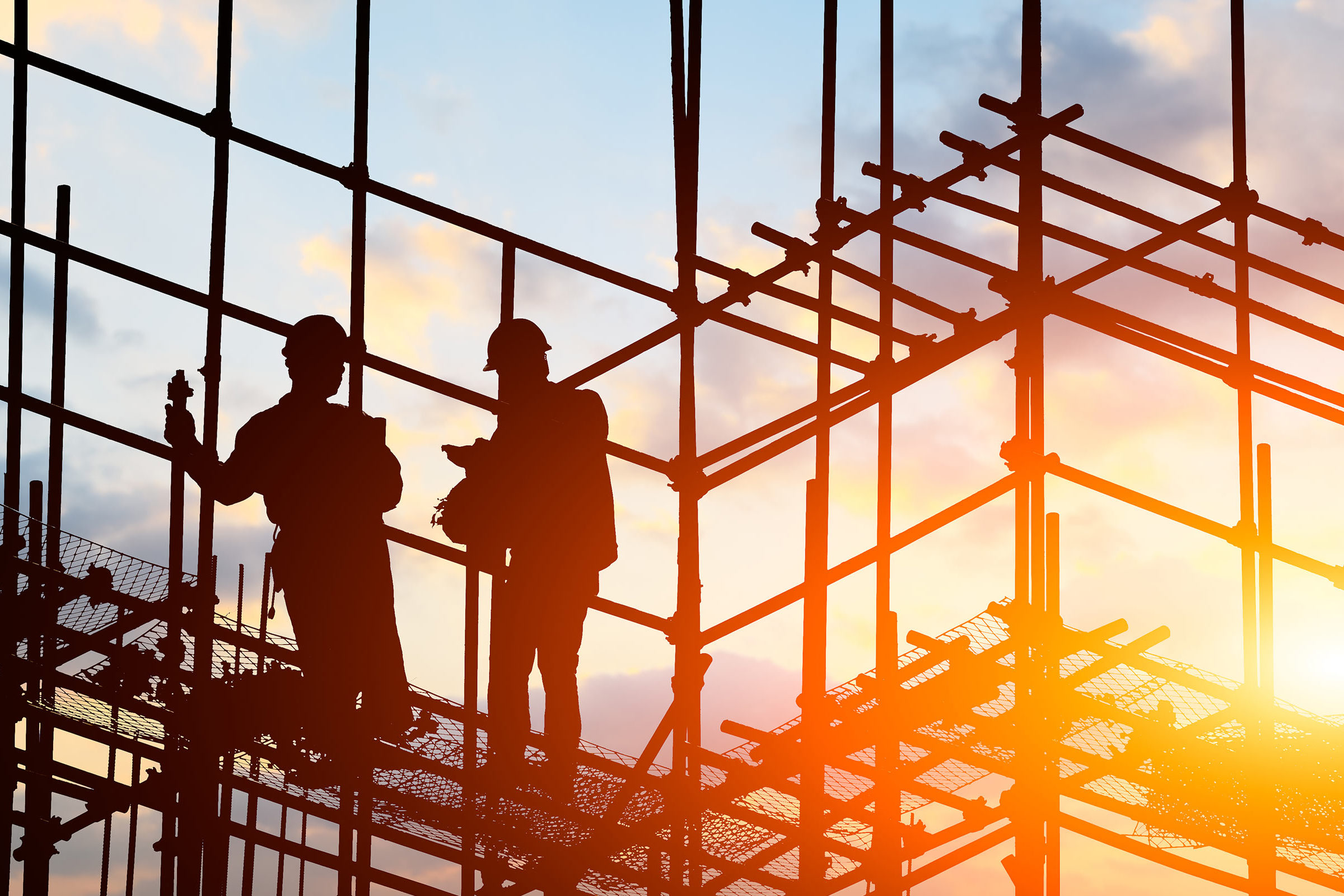 Two construction workers standing on scaffolding at sunrise