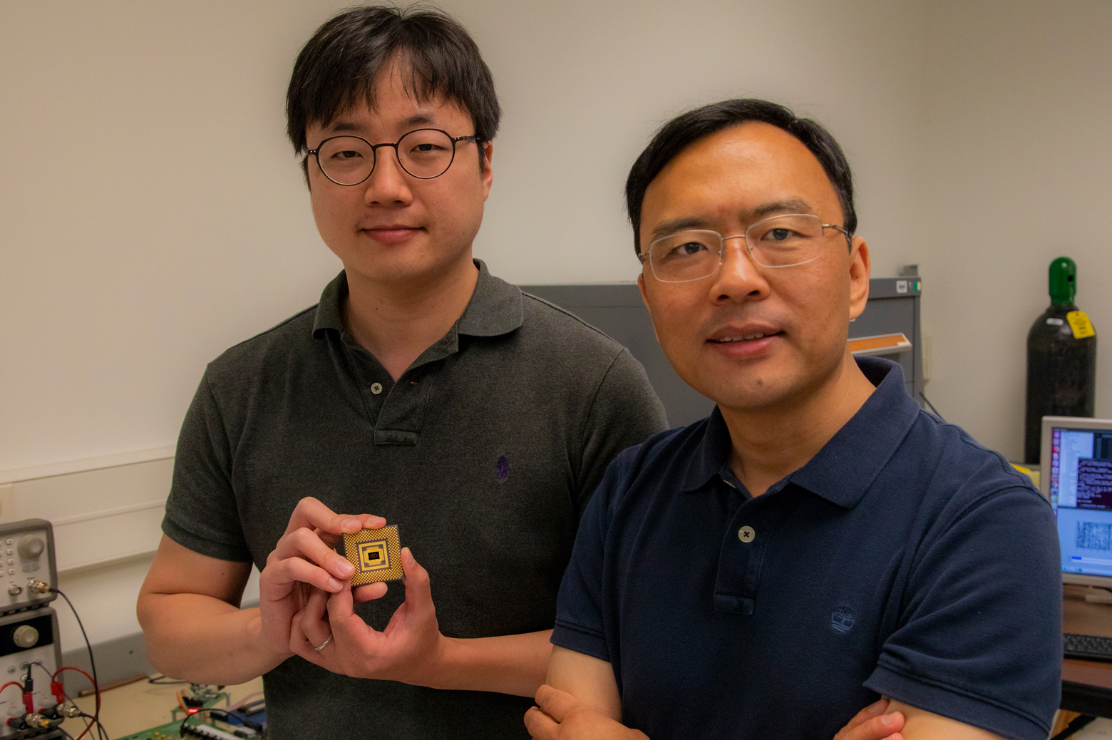 Wei Lu stands with first author Seung Hwan Lee, an electrical engineering PhD student, who holds the memristor array. Photo: Robert Coelius, Michigan Engineering Communications & Marketing