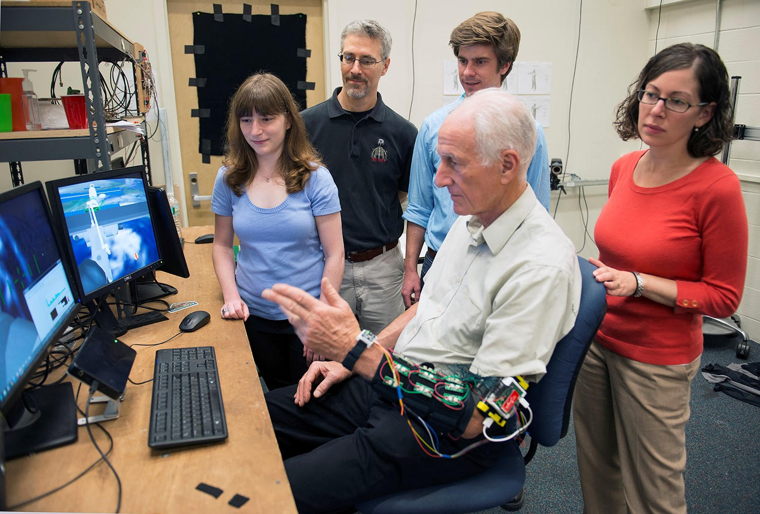 Leia Strling (Right) and other MIT and NASA Jet Propulsion Lab researchers along with former Astronaut Jeff Hoffman use a sensor sleeve to evaluate a gesture interface system for controlling a simulated robotic arm.