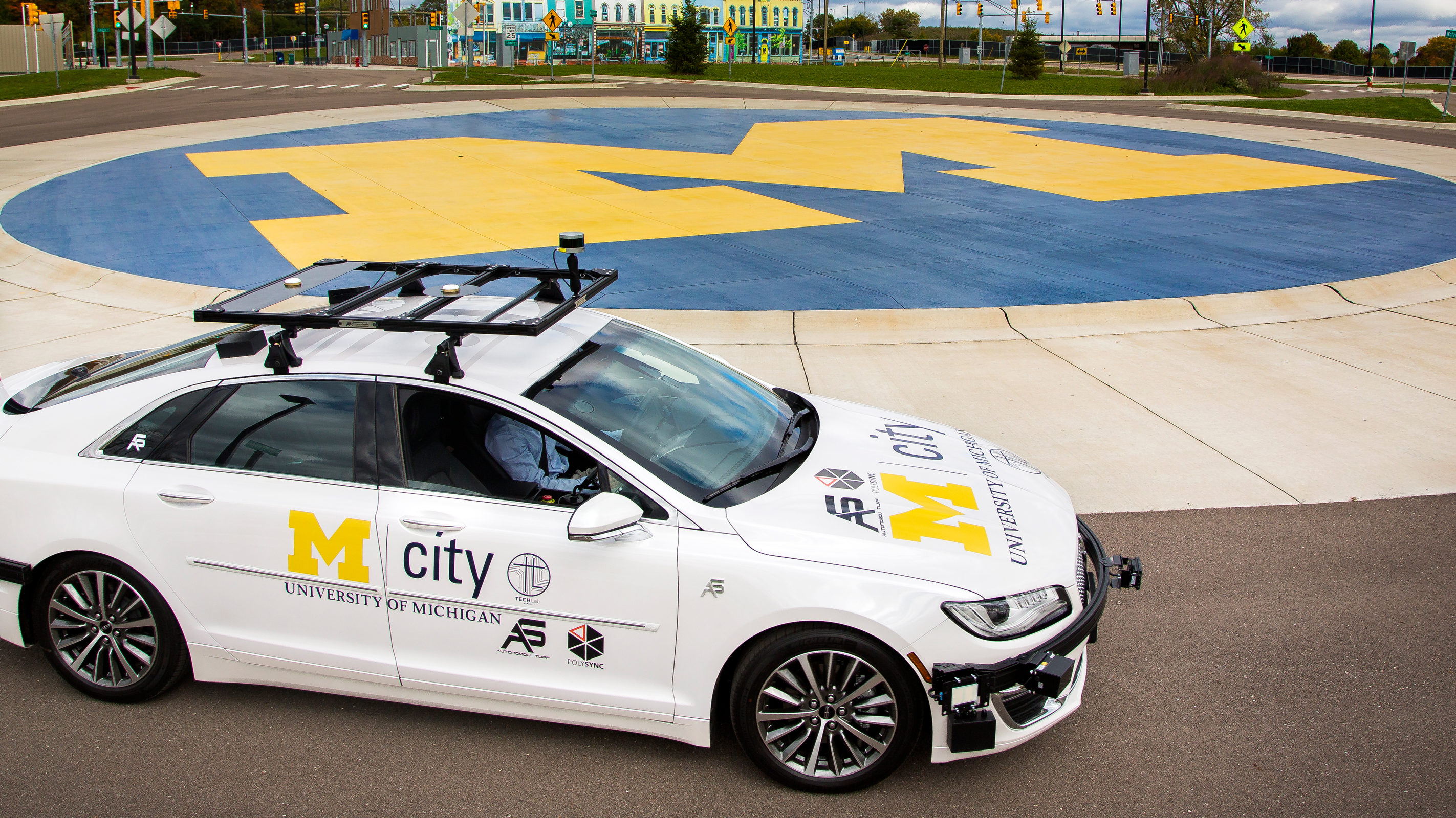 A white Mcity car parked in a circular drive painted with the Michigan logo
