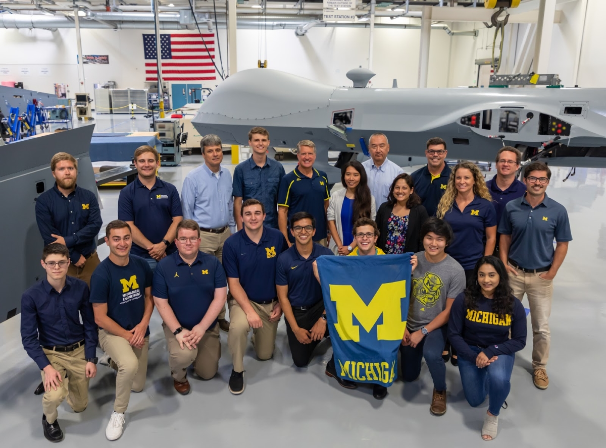 A group of Michigan students and alumni pose at the General Atomics workplace