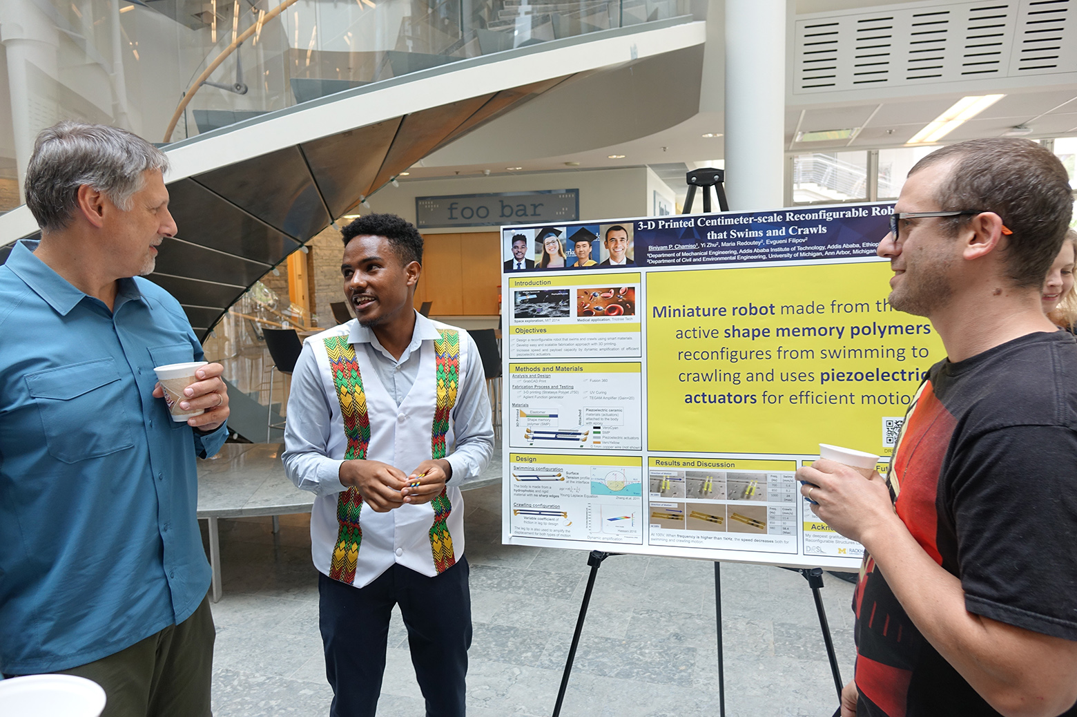 Astudent shows a poster to two faculty