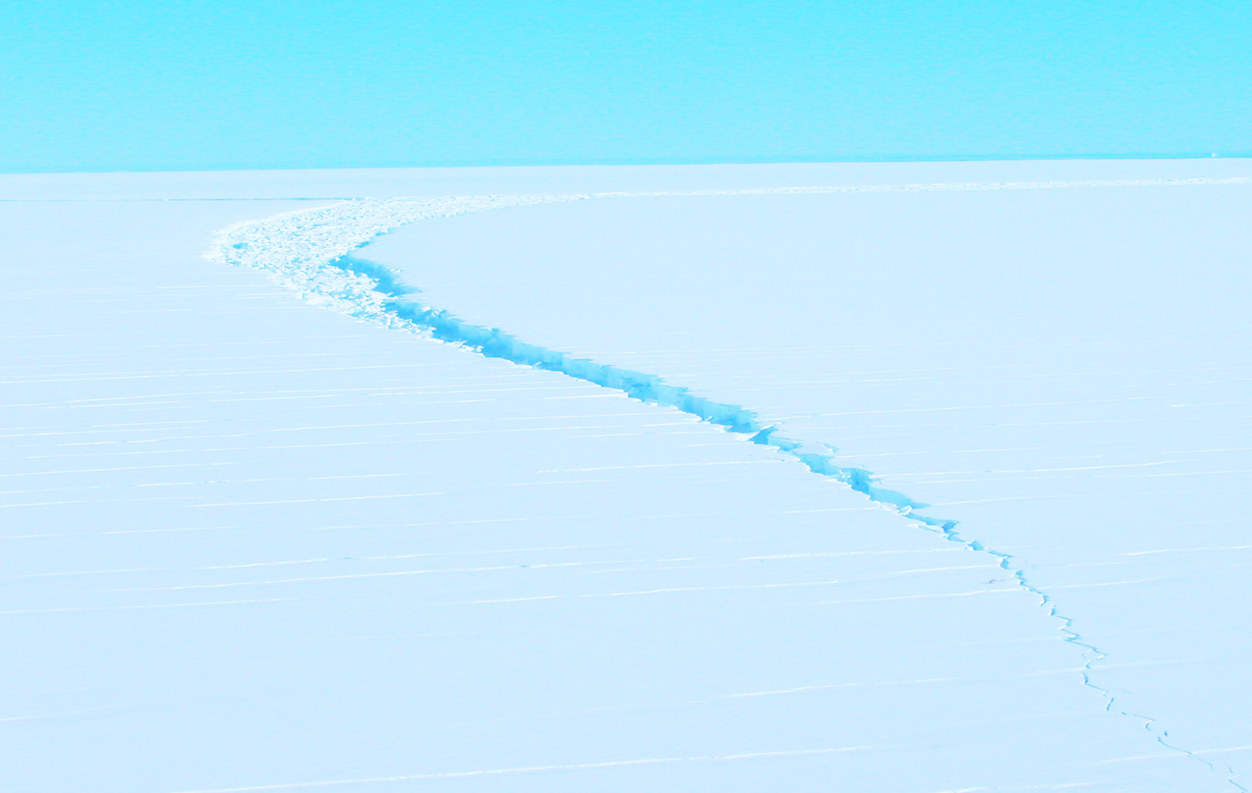 A crack in the Amery Ice Shelf in Antarctica, taken by helicopter. Ice shelves near both of the planet's poles are disintegrating at unexpectedly rapid rates. Photo by Jim Behrens. ​