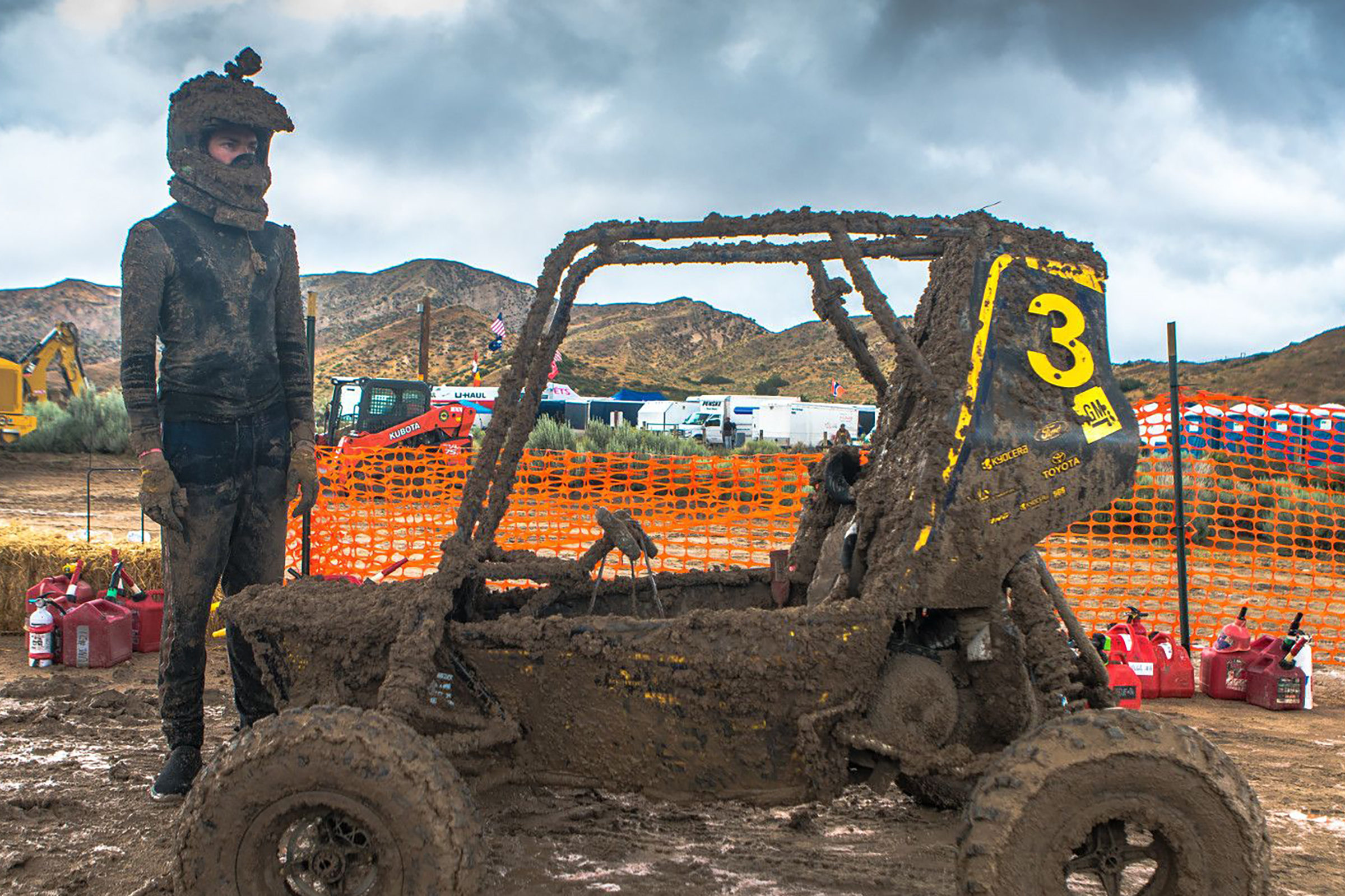 Driver with Baja Car covered in mud