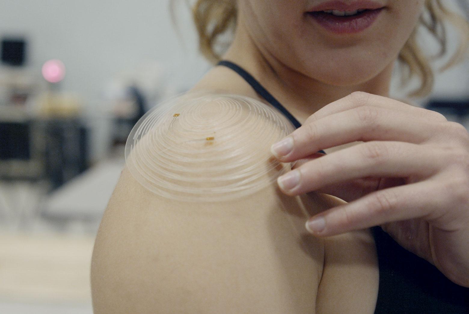 Erin Eyke shows a kirigami sensor worn on her bare shoulder