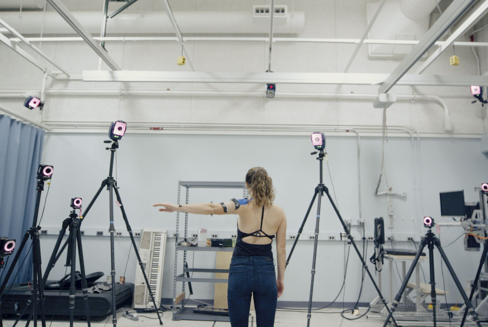 Woman stands in the middle of a room full of cameras, holding out her arm