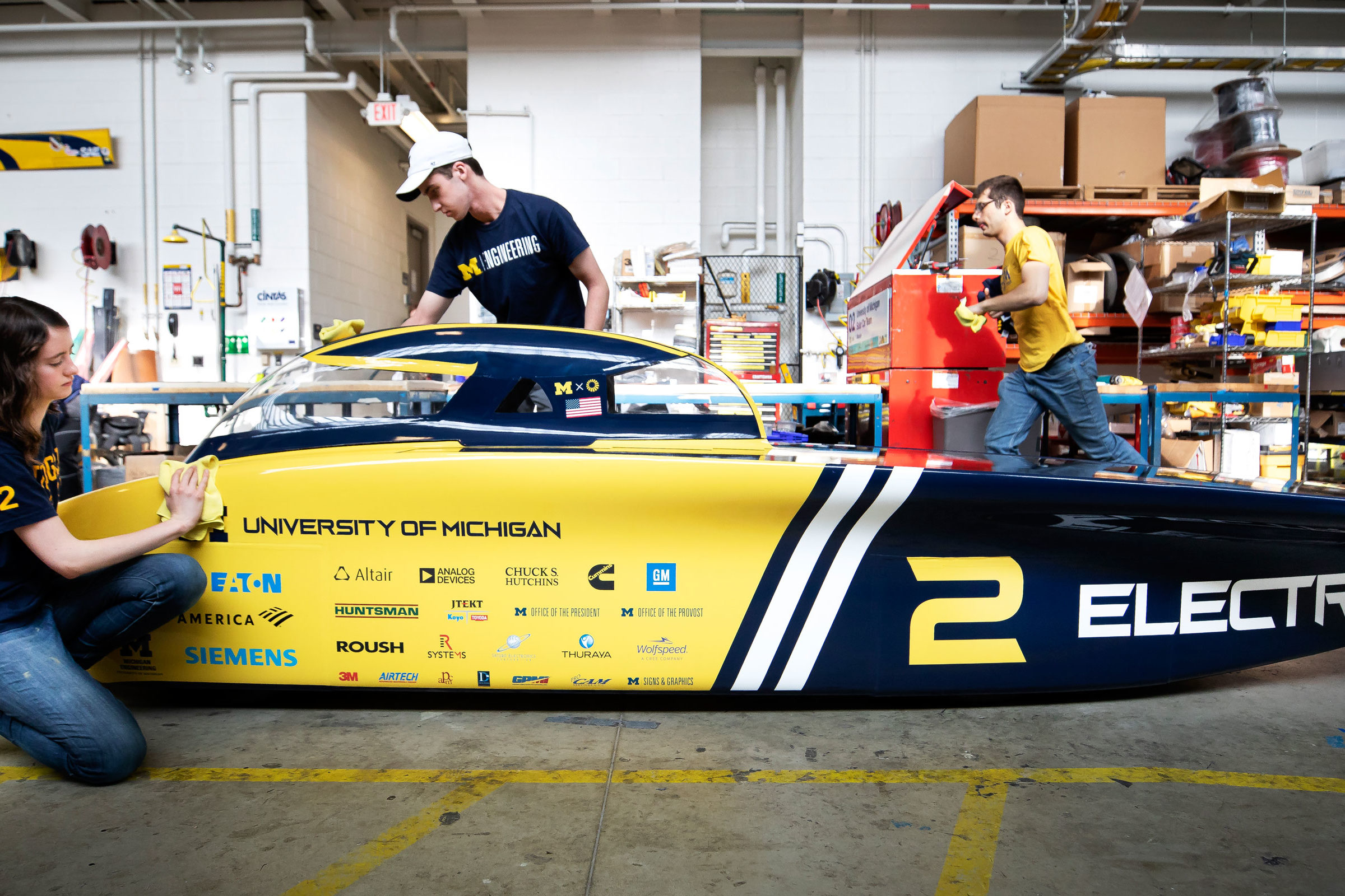 Members of the solar car team make final touches to the vehicle