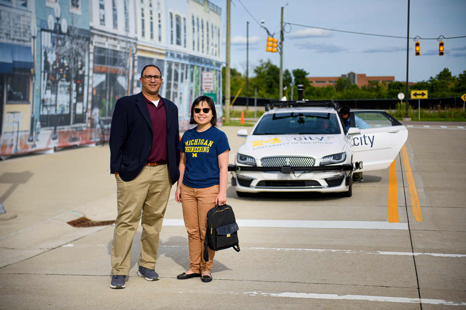 Professors Lionel Robert and X. Jessie Yang stand in front of an autonomous vehicle at Mcity