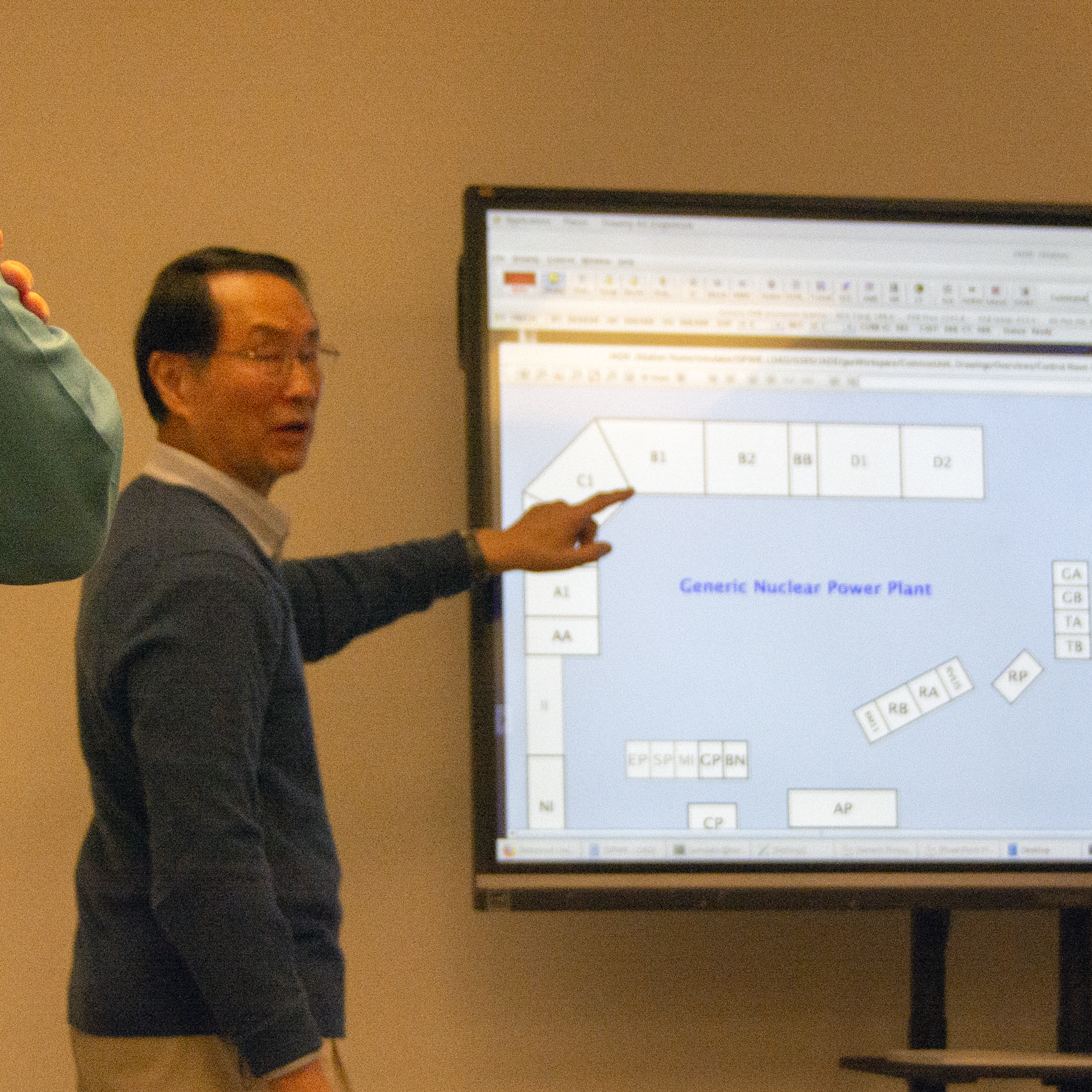 Professor Lee points to a screen that is displaying the simulation software.