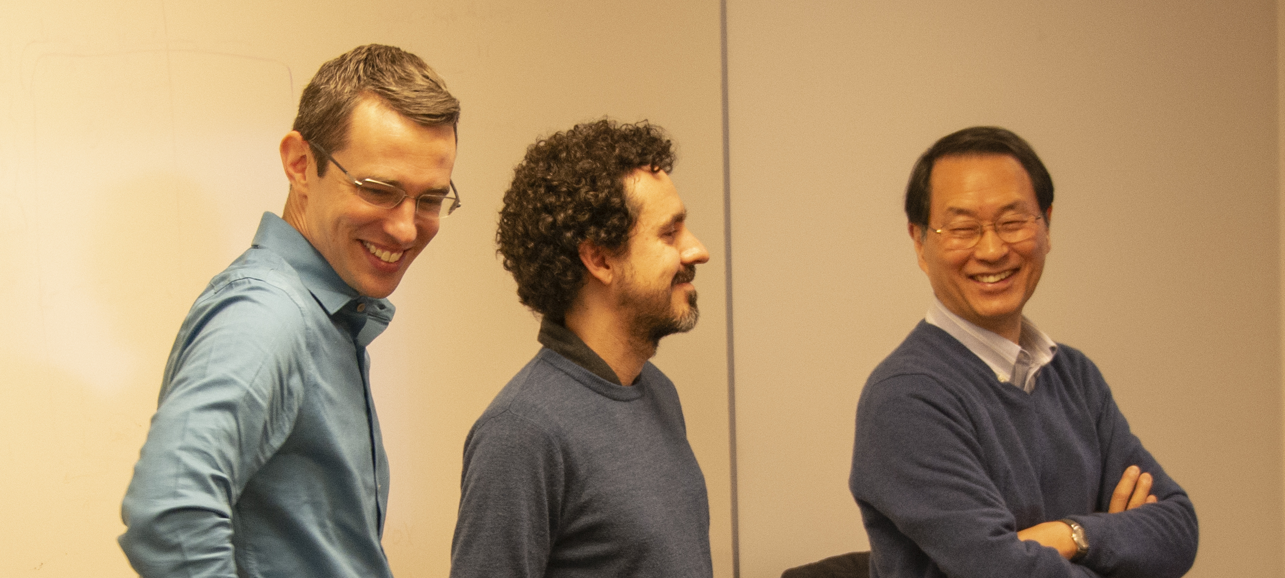 Two faculty and a student have a chuckle in a laboratory.