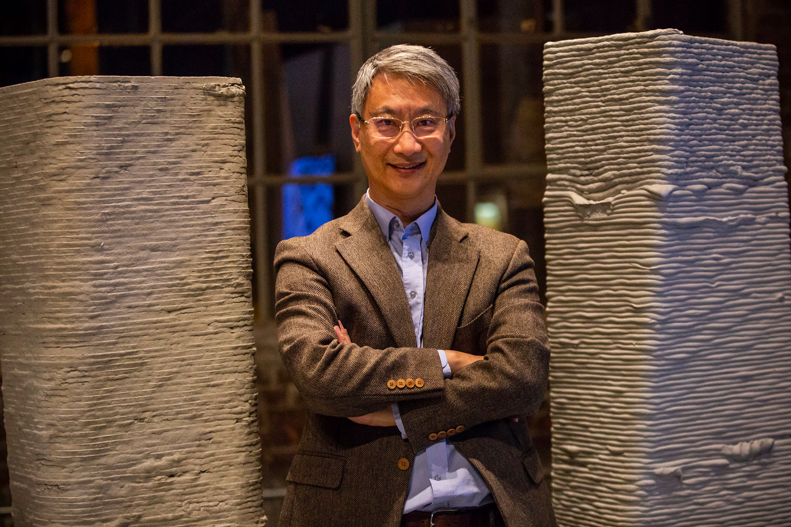 Victor Li stands in front of 3D printed concrete