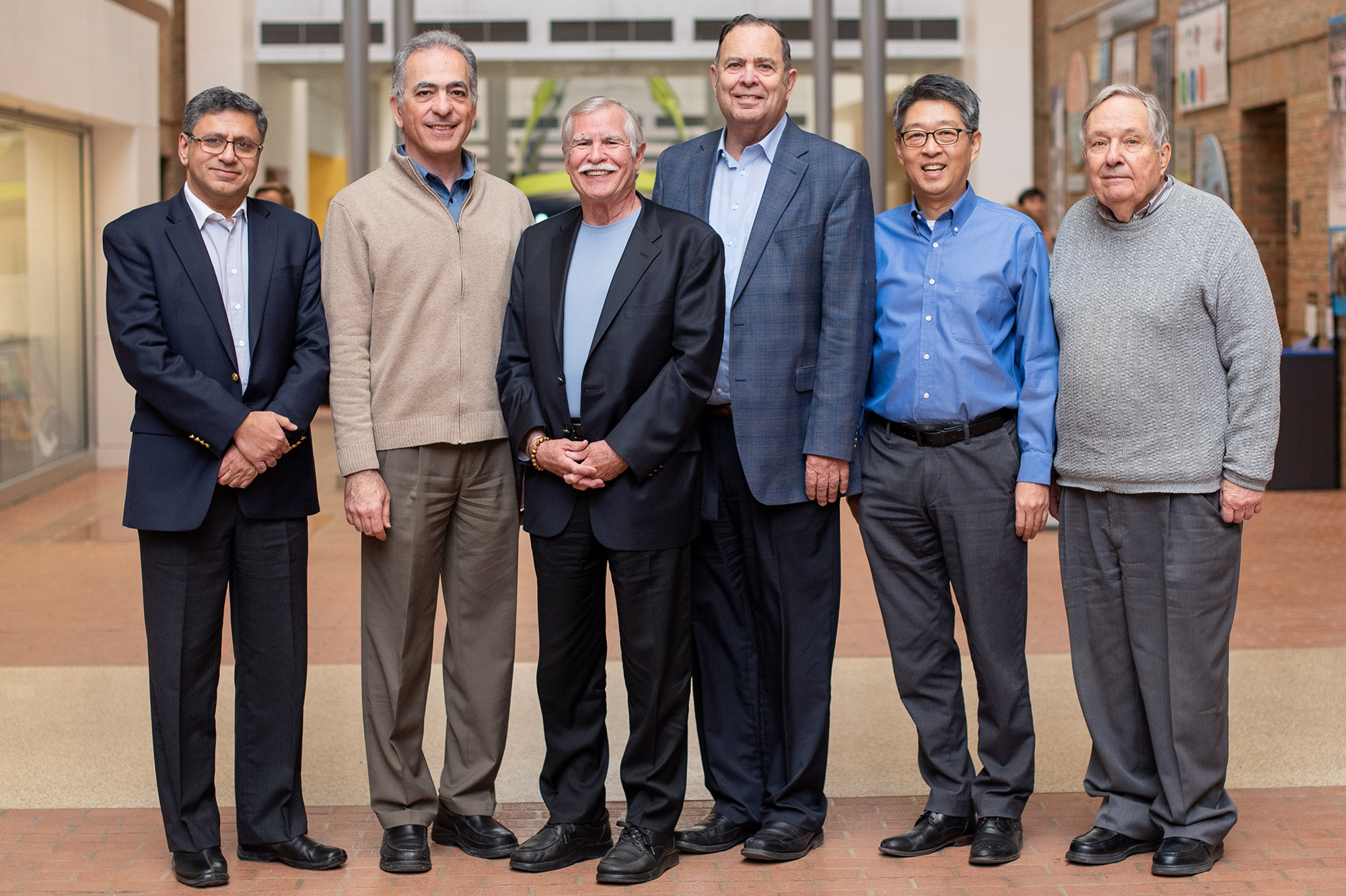 Dr. Kurt Petersen stands with a group of current and former faculty