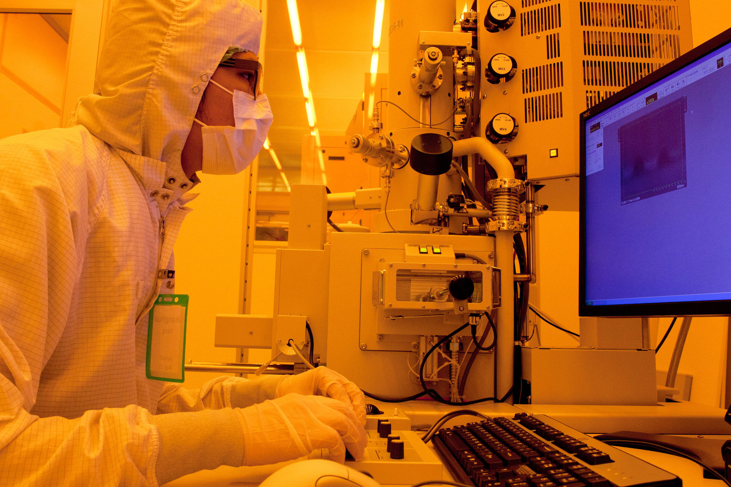 Scientist in the Lurie Nanofabrication Facility uses a computer inside of a clean room