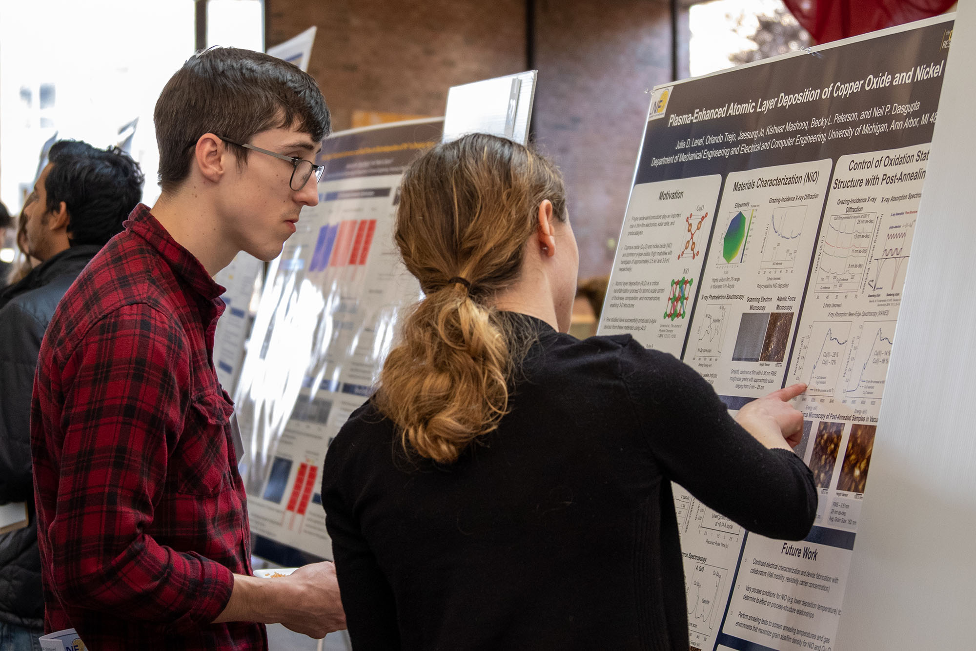 Two students examine a poster during the symposium