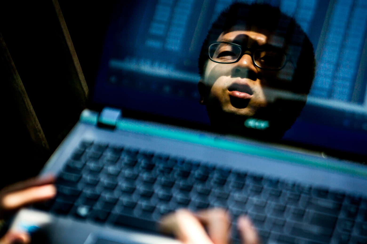 Qi Luo's face is reflected in the screen of a laptop
