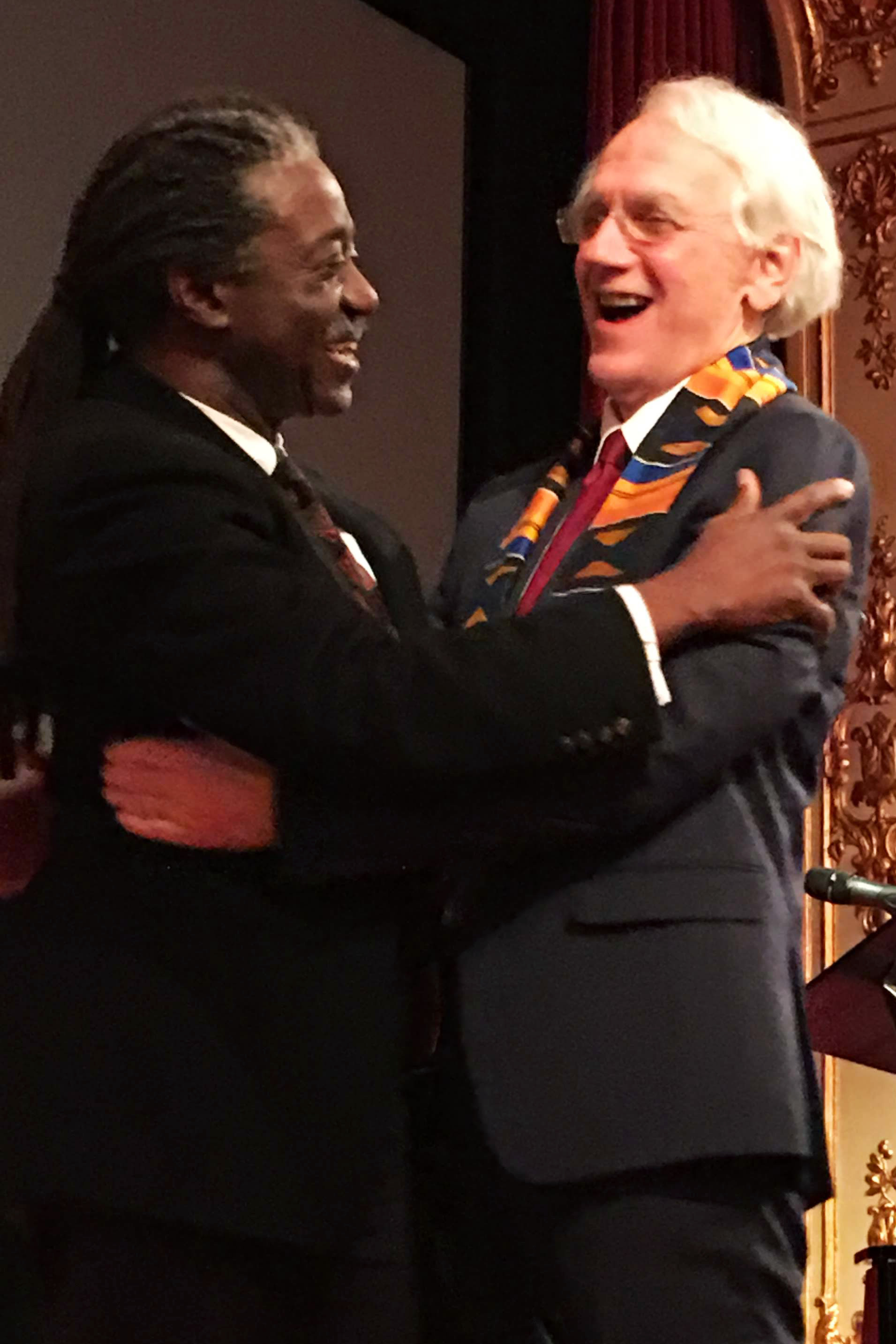 Herbert Winful and Gérard Mourou hug at at party for the 2018 Nobel Ceremony
