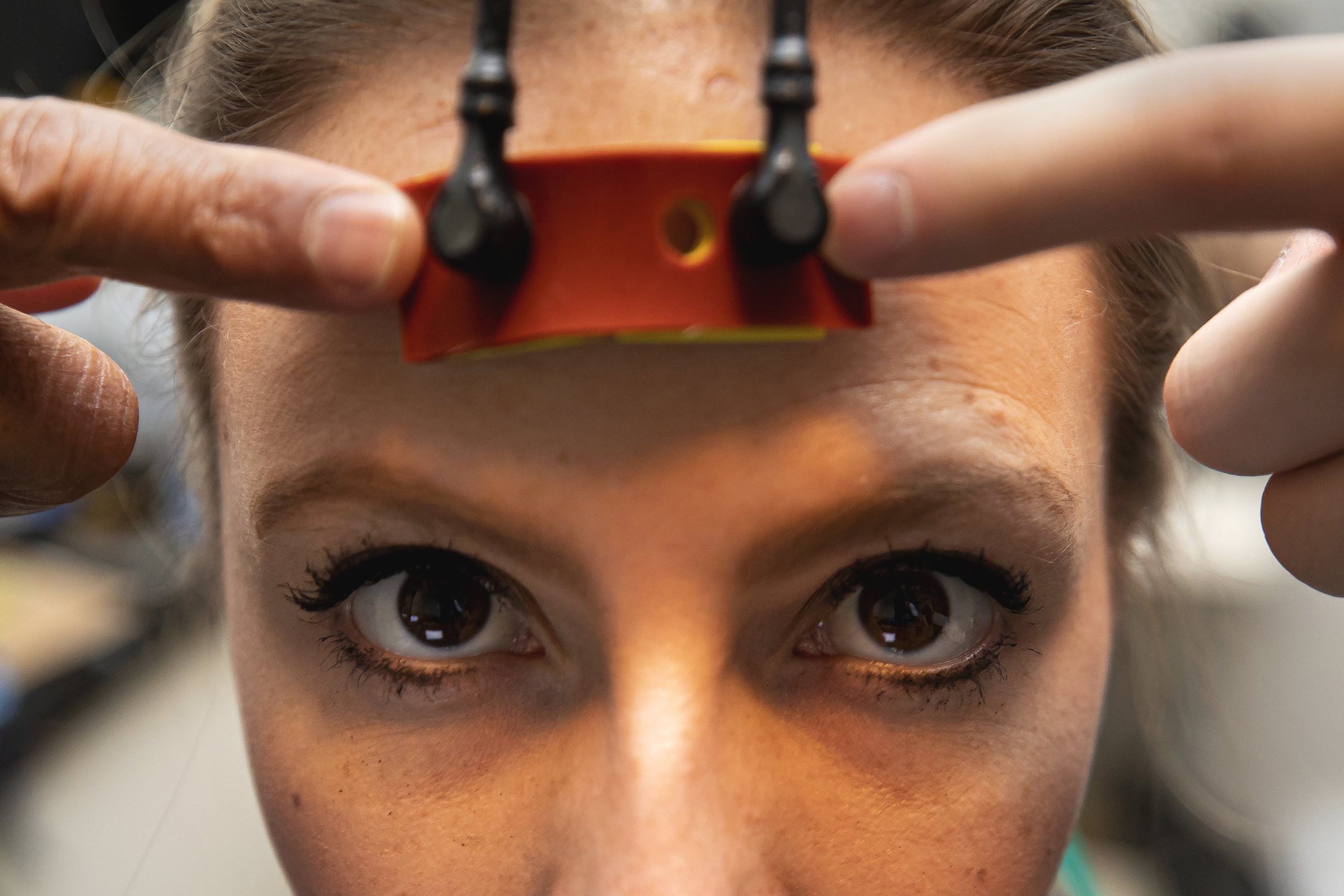 Woman with portable concussion detector device on her forehead