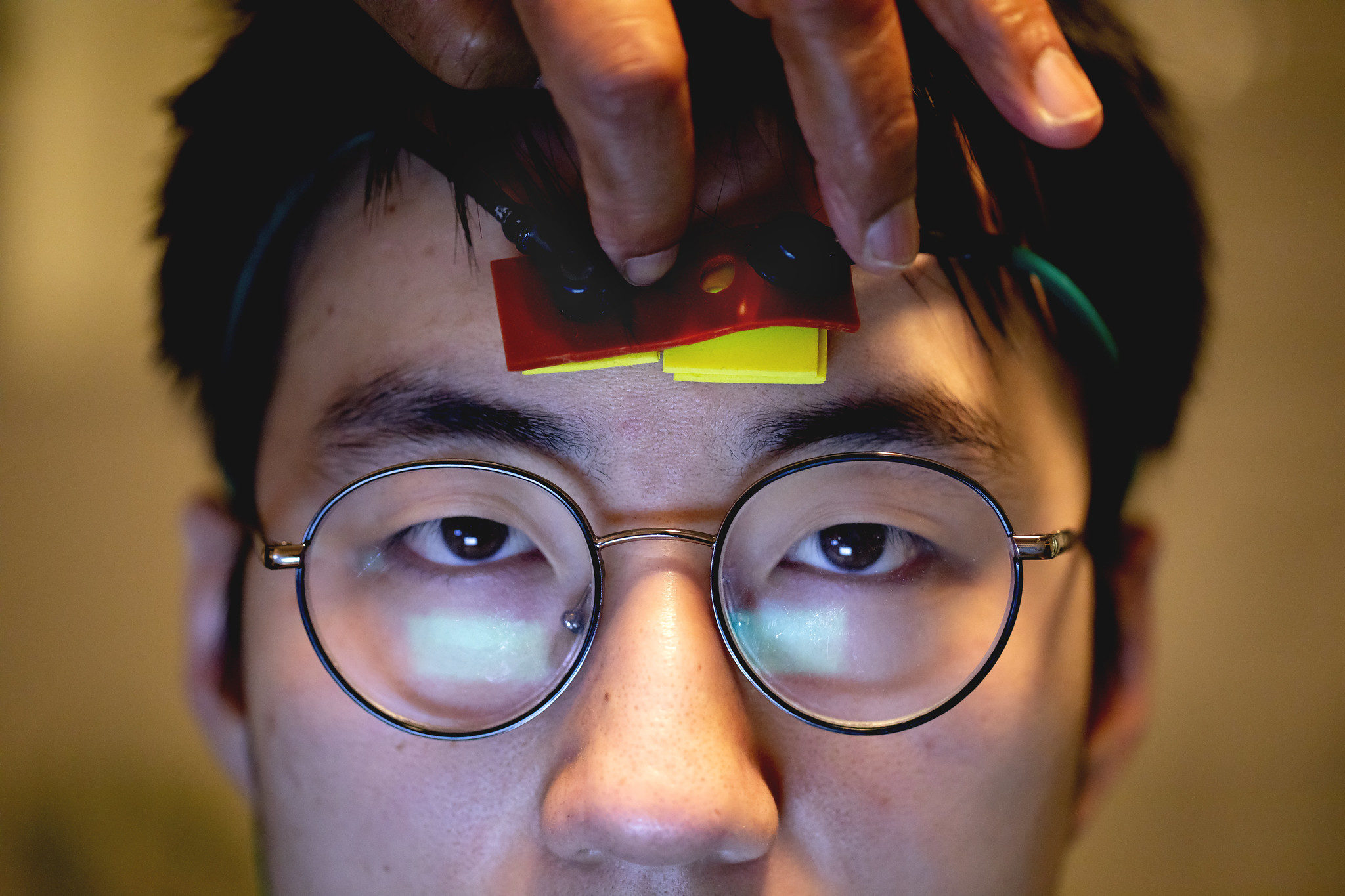 A photograph of a student wearing a probe that detects concussions through light.
