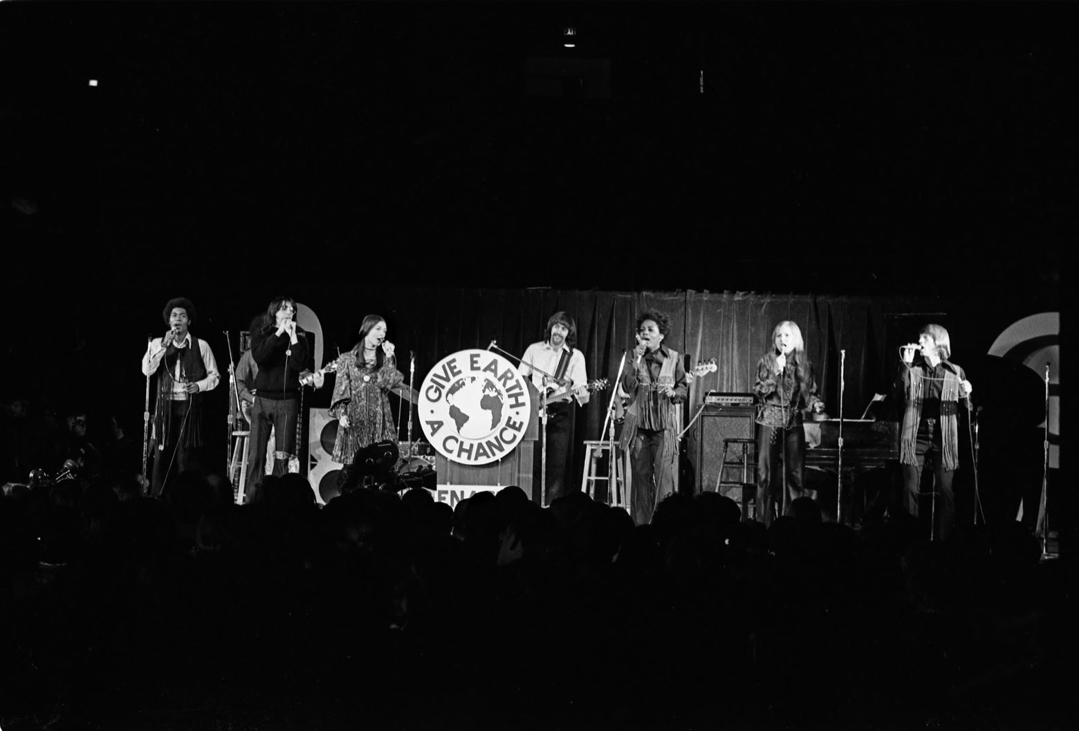 black and white photo of people standing on stage