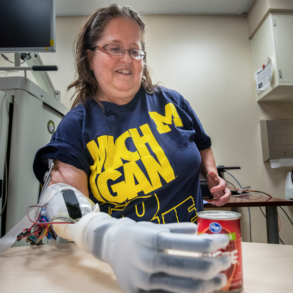 Woman grabs a can with prosthetic arm