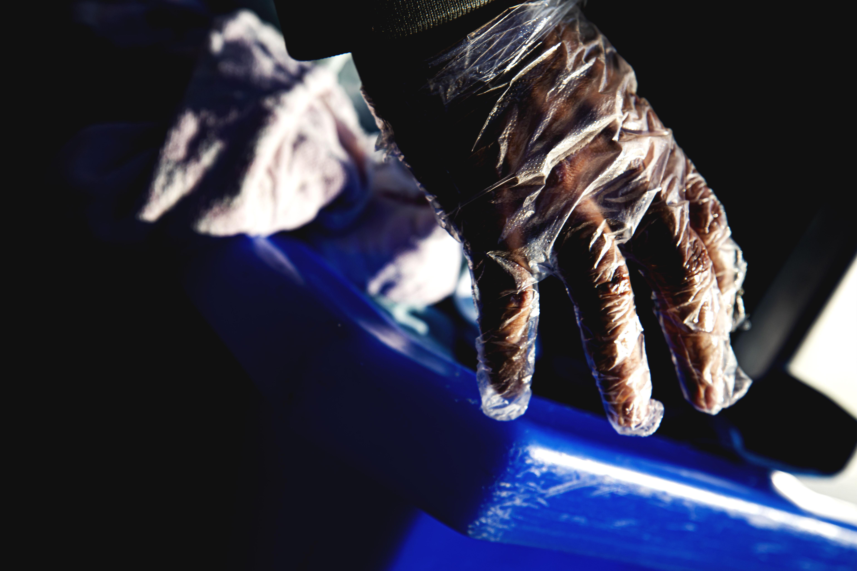 a student wearing gloves handles dorm furniture.