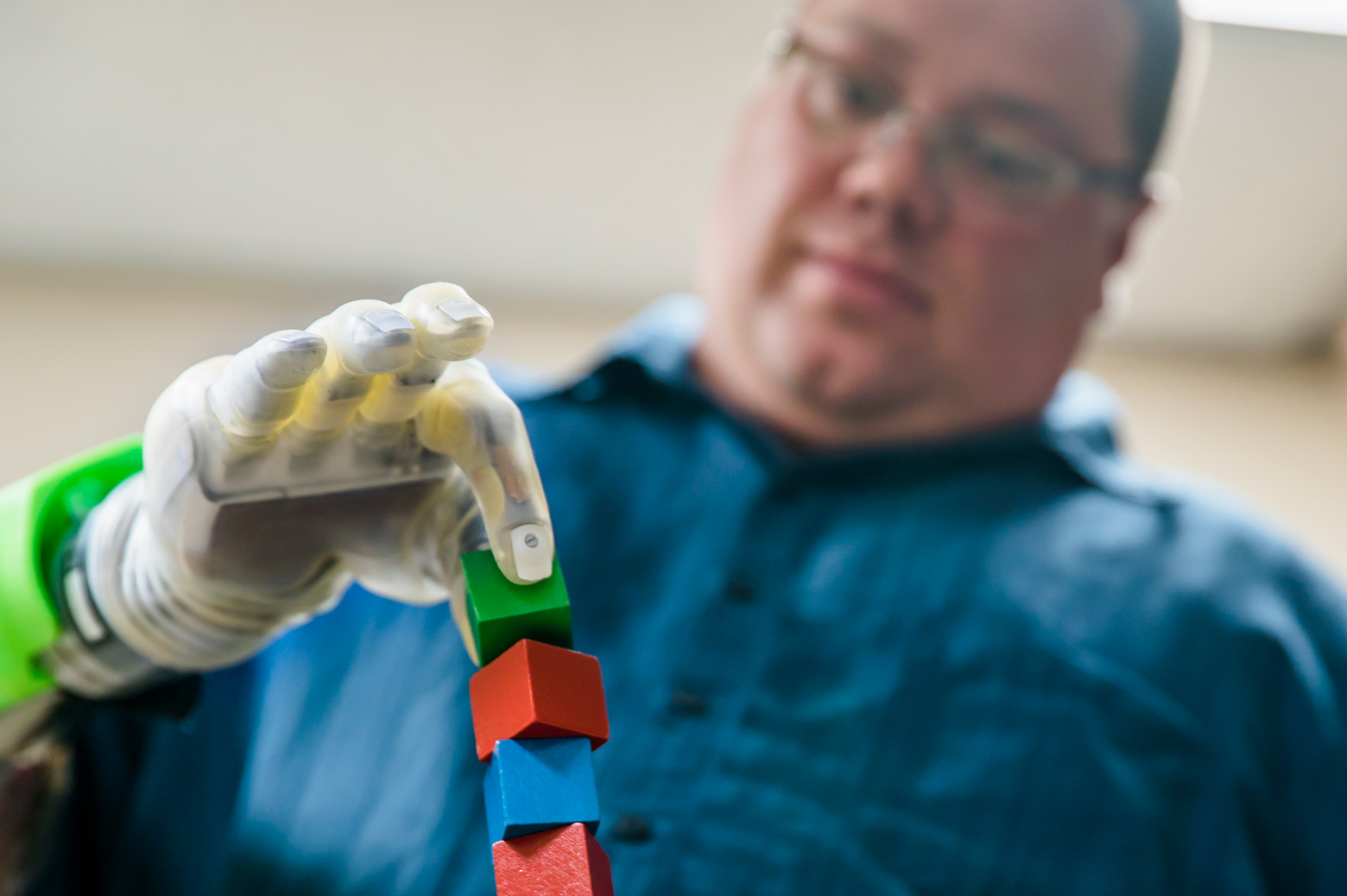 A man stacks cubes using a prosthetic arm