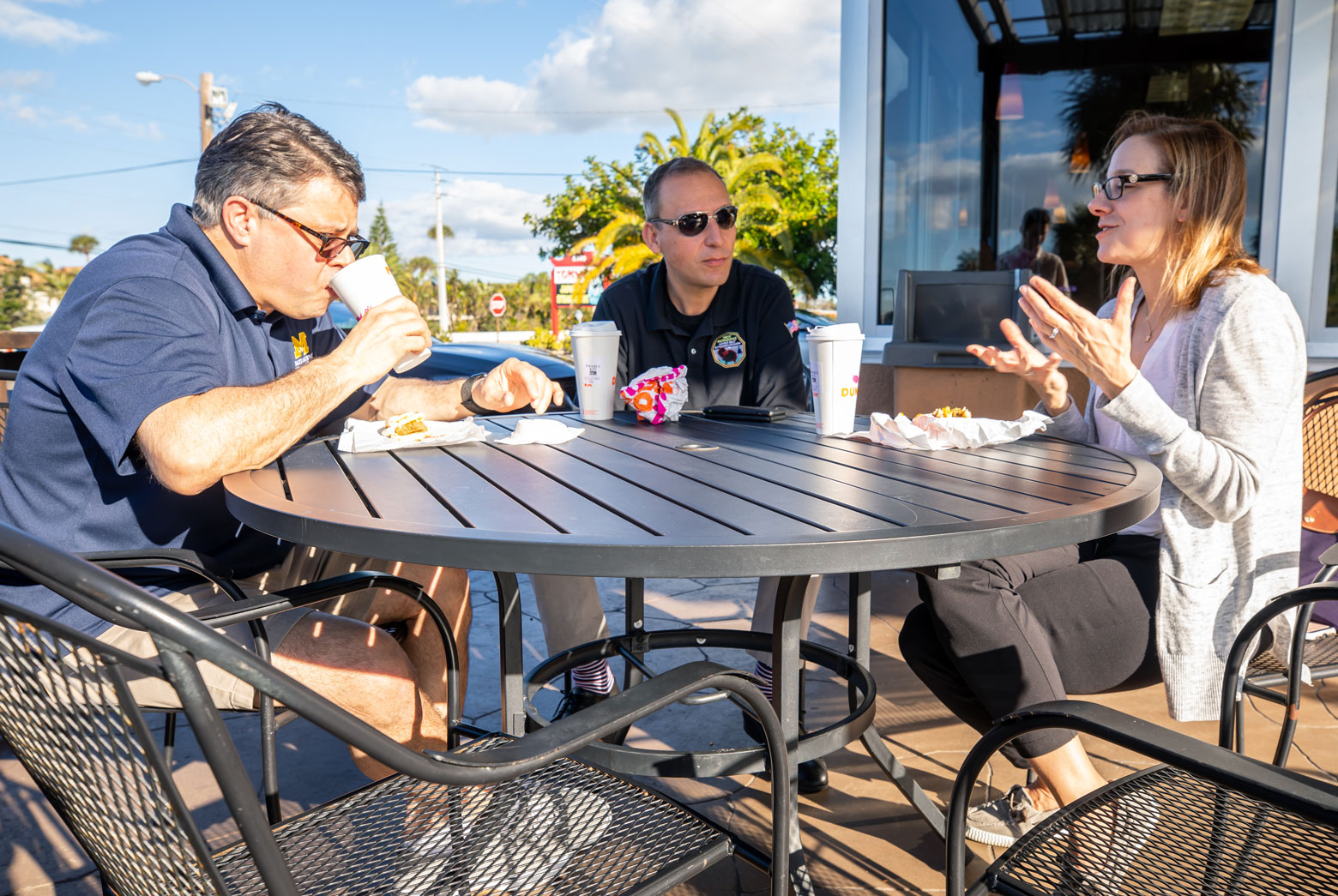 Three adults eat together at a table outside