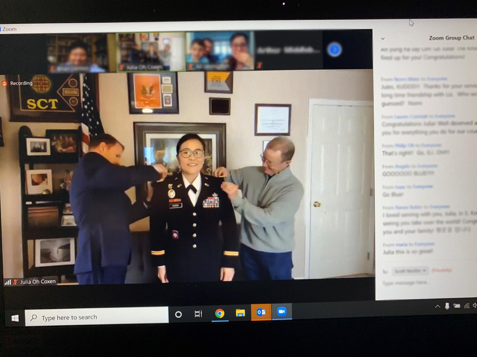 Photo of Julia Coxen receiving having her new rank insignia pinned to her uniform within a virtual chat setting