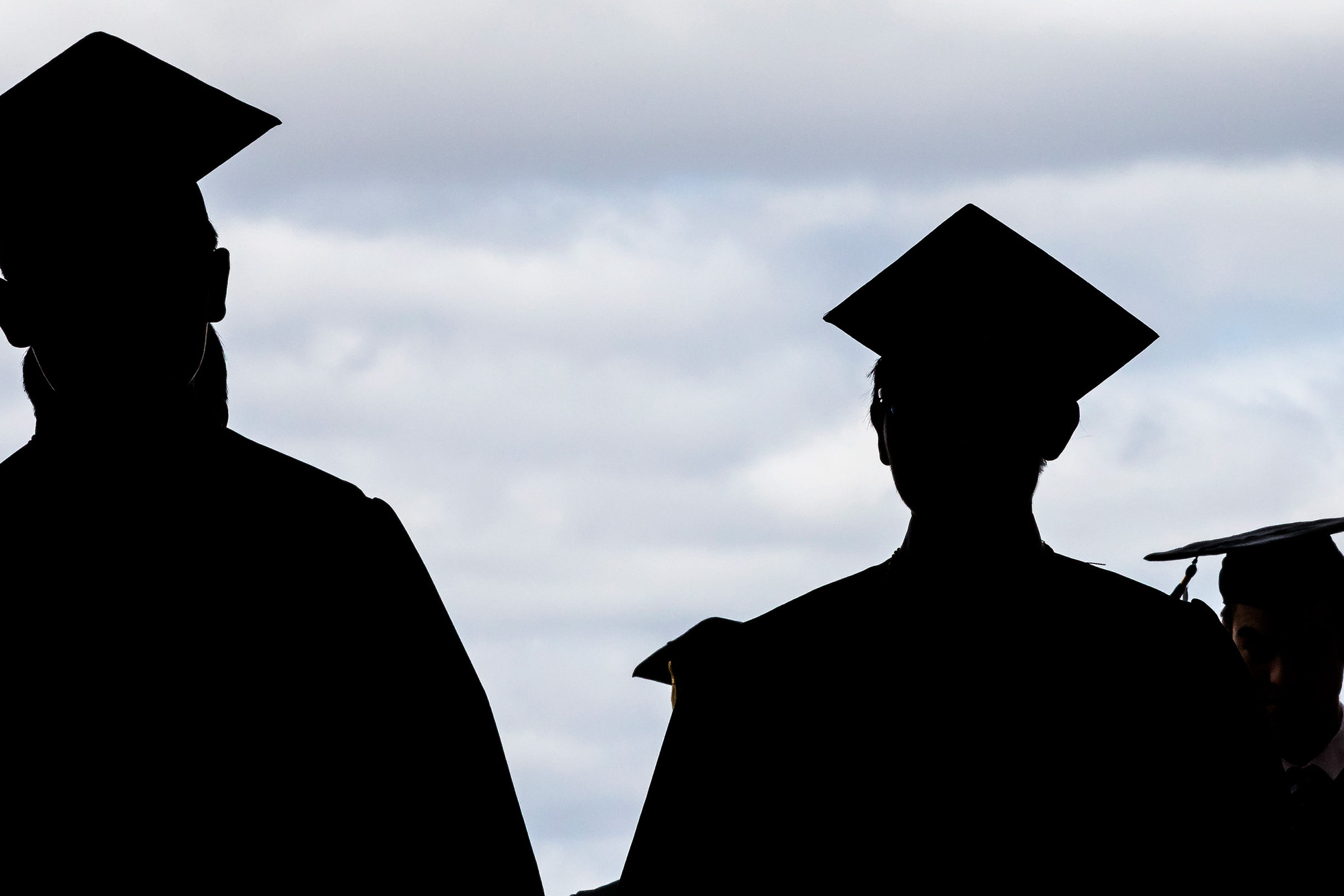 Silhouette of graduates in caps and gowns