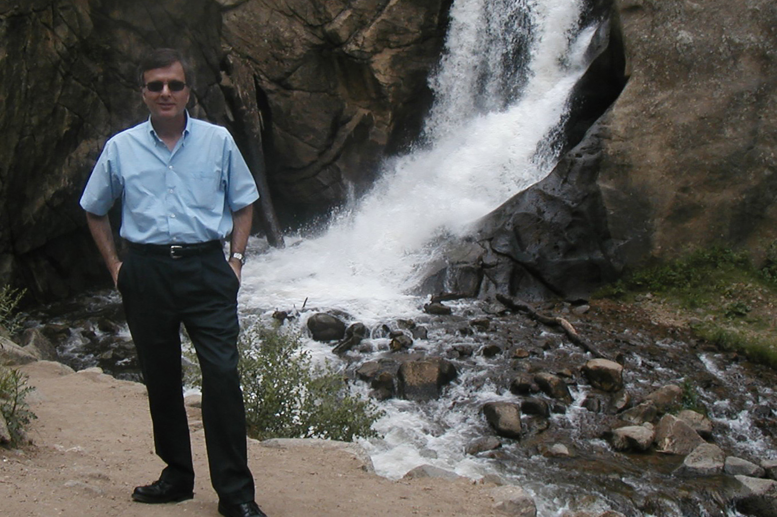 NIk Katopodes stands in front of a waterfall in Boulder, CO