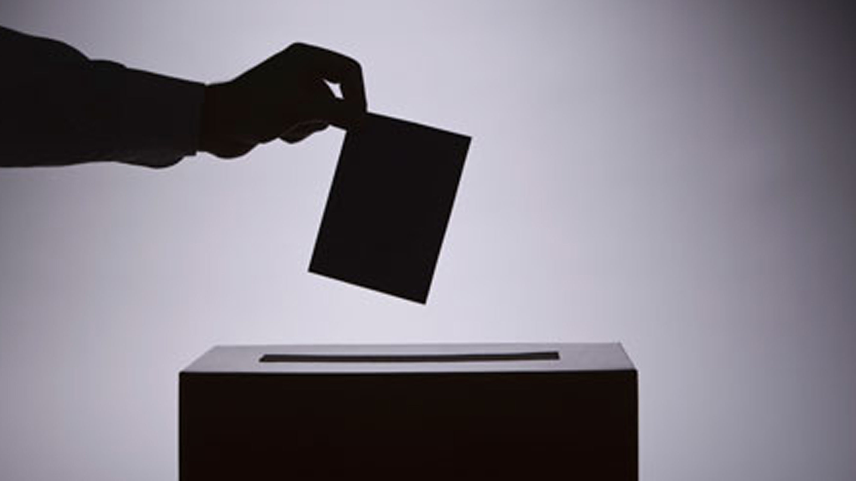 hand places ballot in box