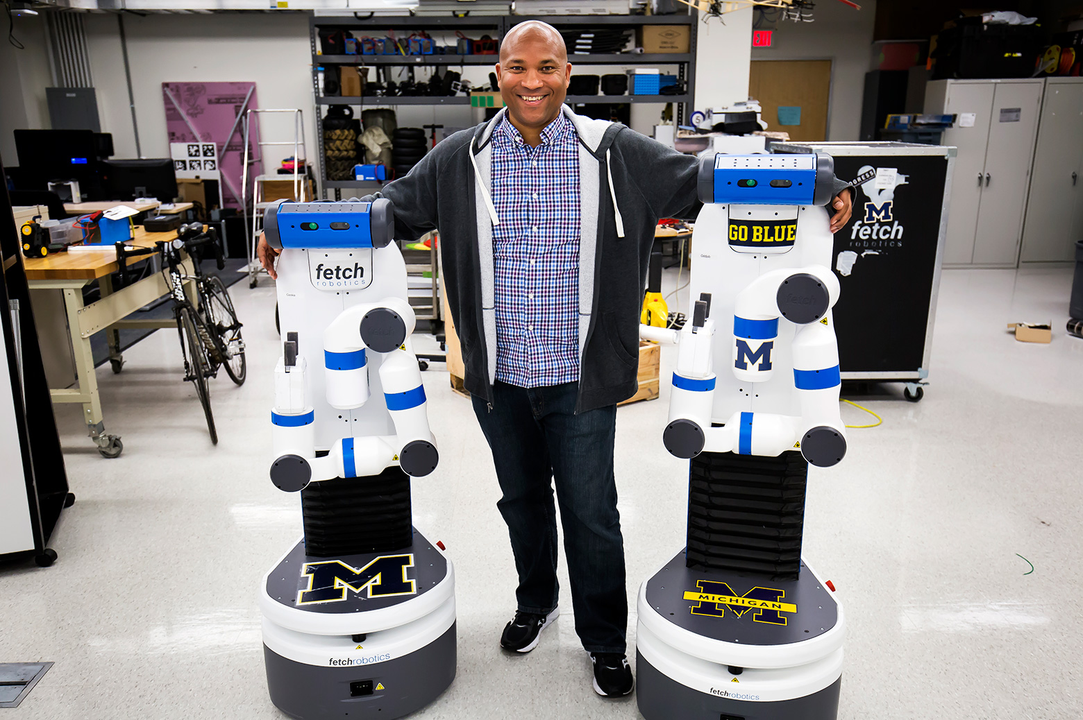 Chad Jenkins, CSE Associate Professor, poses with his research group's two robots, Odd Job and Cookie.