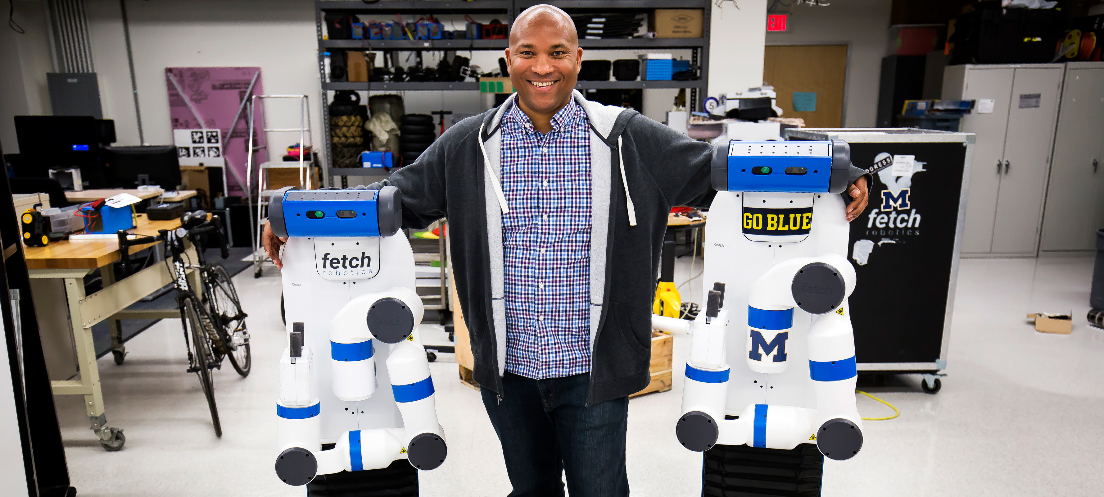 Chad Jenkins, CSE Associate Professor, poses with his research group's two robots, Odd Job and Cookie, in the Beyster Building on October 27, 2016