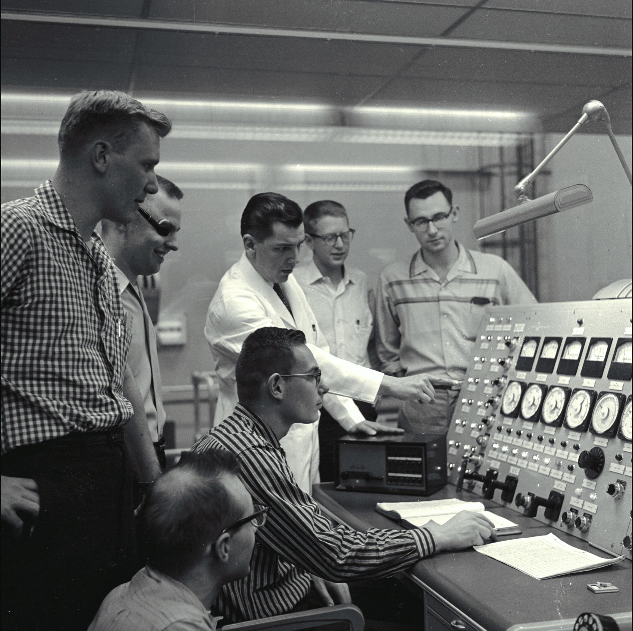 students and a teacher looking over a a large panel with dials and knobs in the late 1950s