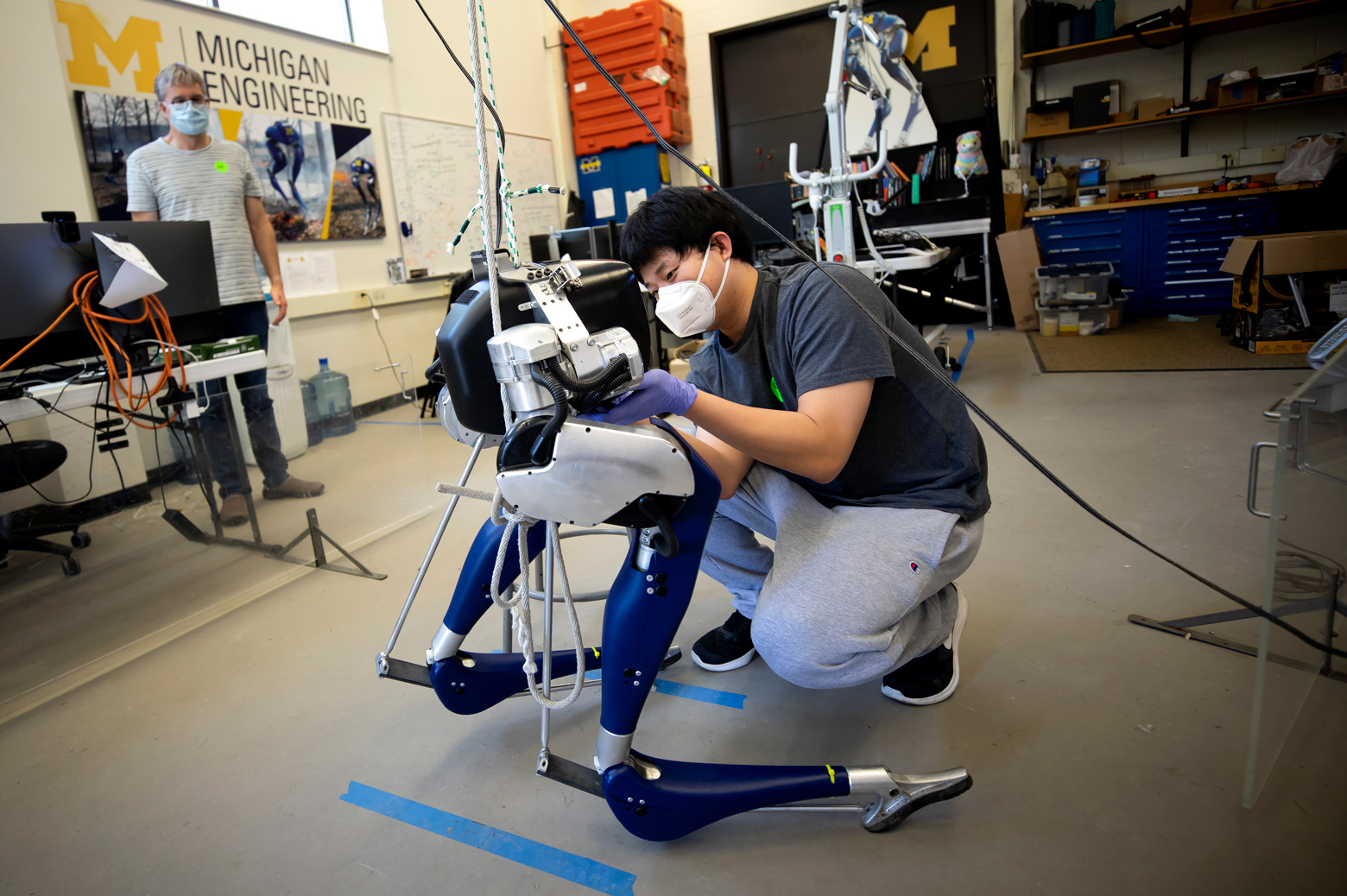 Yukai Gong, Robotics PhD Student, installs a battery into Cassie, a bipedal robot, as Jessy Grizzle, Director of the Robotics Institute, looks on in their lab on North Campus of the University of Michigan in Ann Arbor, MI on May 26, 2020.