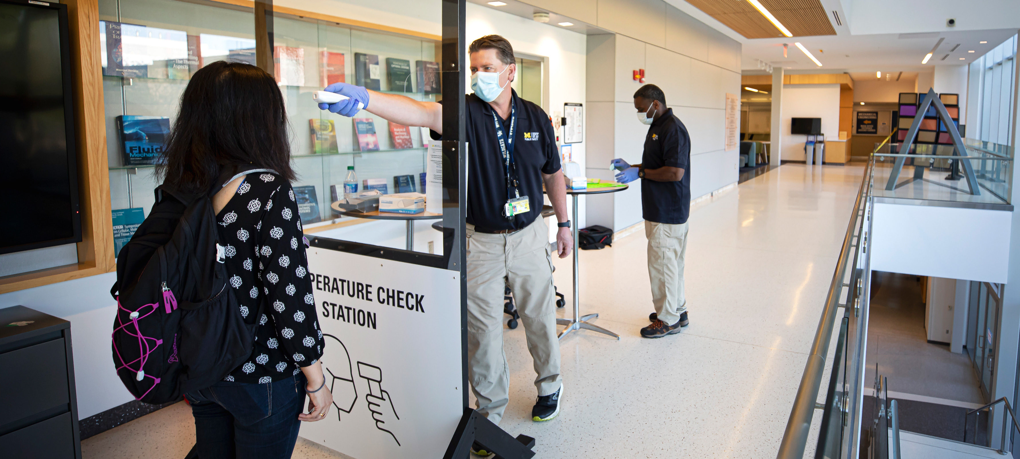 Shilva Shrestha, Environmental Engineering PhD Student, has her temperature checked by Bryan Daniels, DPSS Quartermaster, at the entrance the G.G. Brown Building on North Campus of the University of Michigan in Ann Arbor, MI on May 26, 2020.