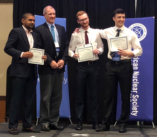 three students holding awards and the president of the society