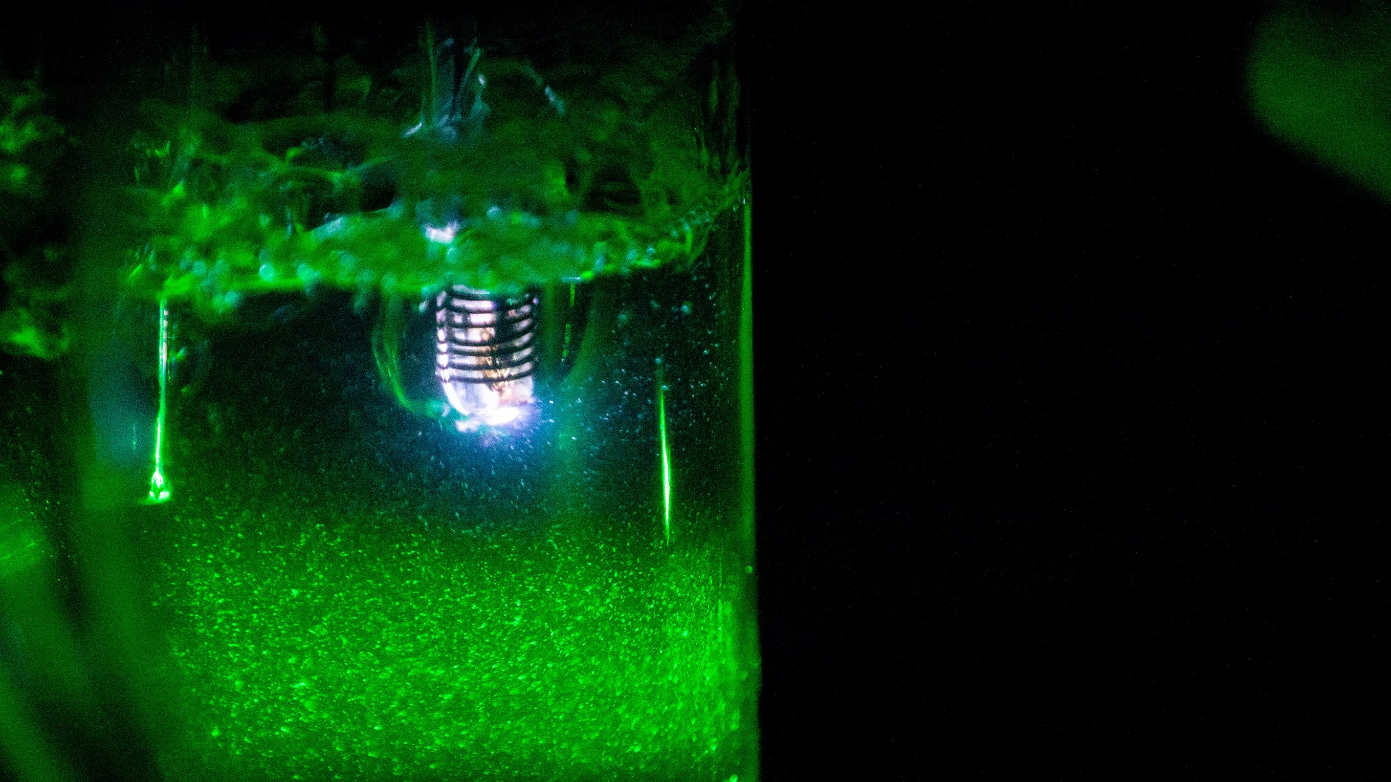 Jar of water glows with green light