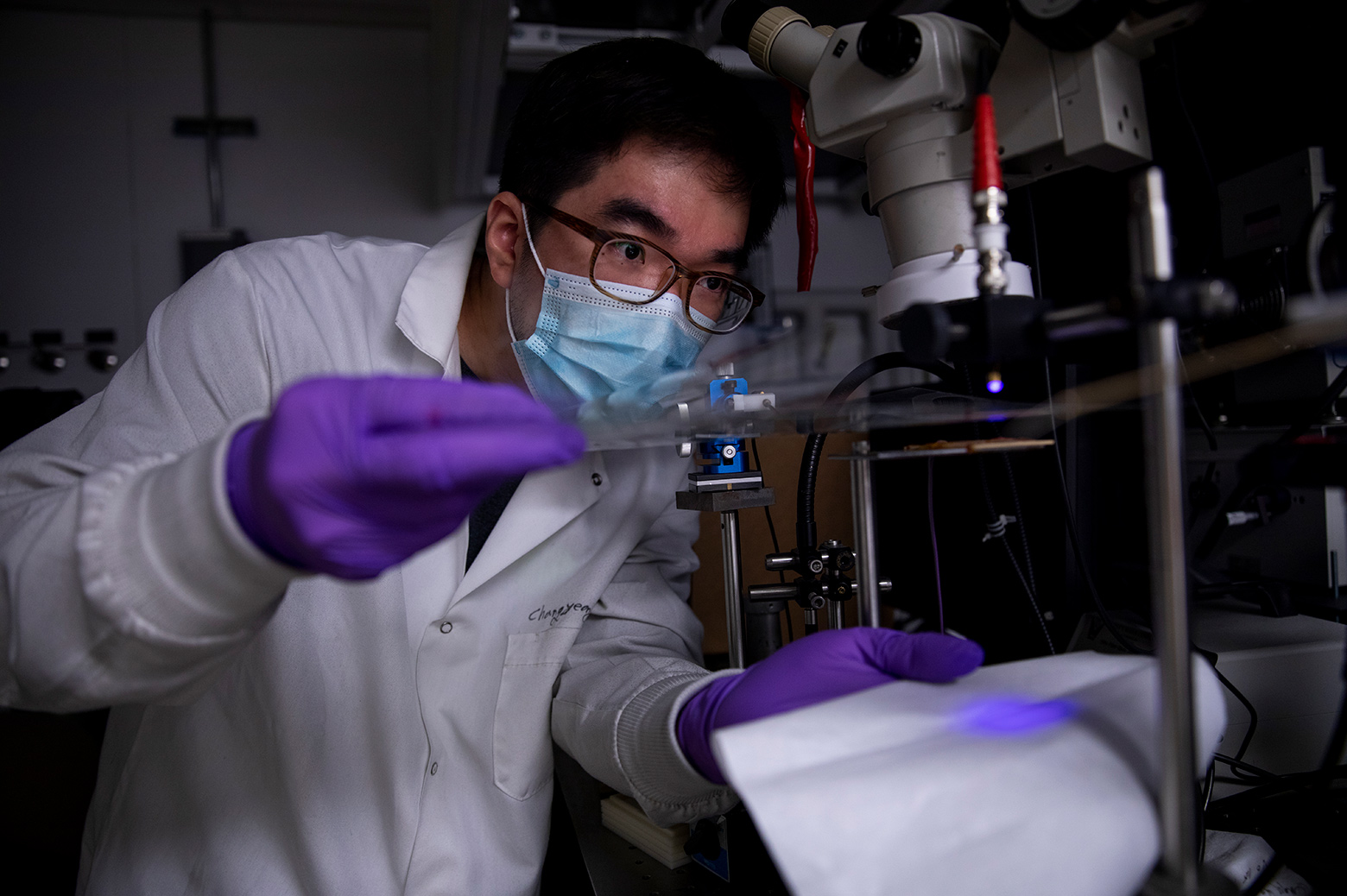 """Changyeong Jeong, a graduate student in electrical engineering and computer science, measures how well light passes through a sheet of flexible transparent conductor. The material sandwiches a thin layer of silver between two """"dielectric"""" materials, aluminum oxide and zinc oxide, producing a conductive anti-reflection coating on the sheet of plastic."""