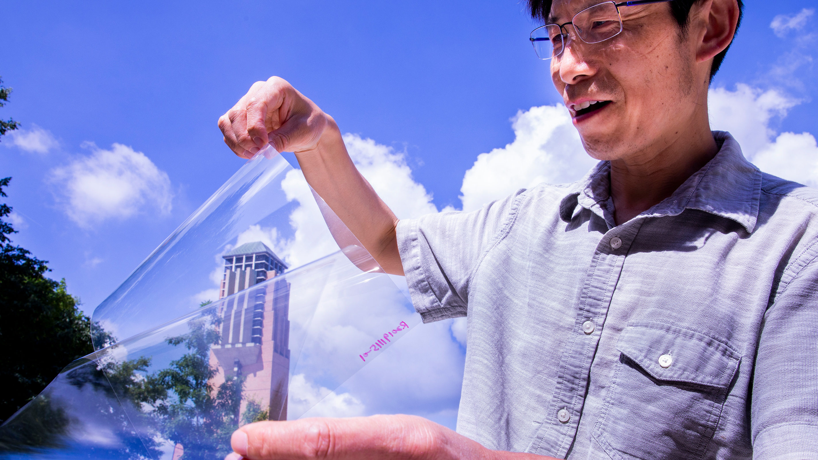 """Jay Guo holds a sheet of flexible transparent conductor on the University of Michigan's College of Engineering North Campus. The material sandwiches a thin layer of silver between two """"dielectric"""" materials, aluminum oxide and zinc oxide, producing a conductive anti-reflection coating on the sheet of plastic."""